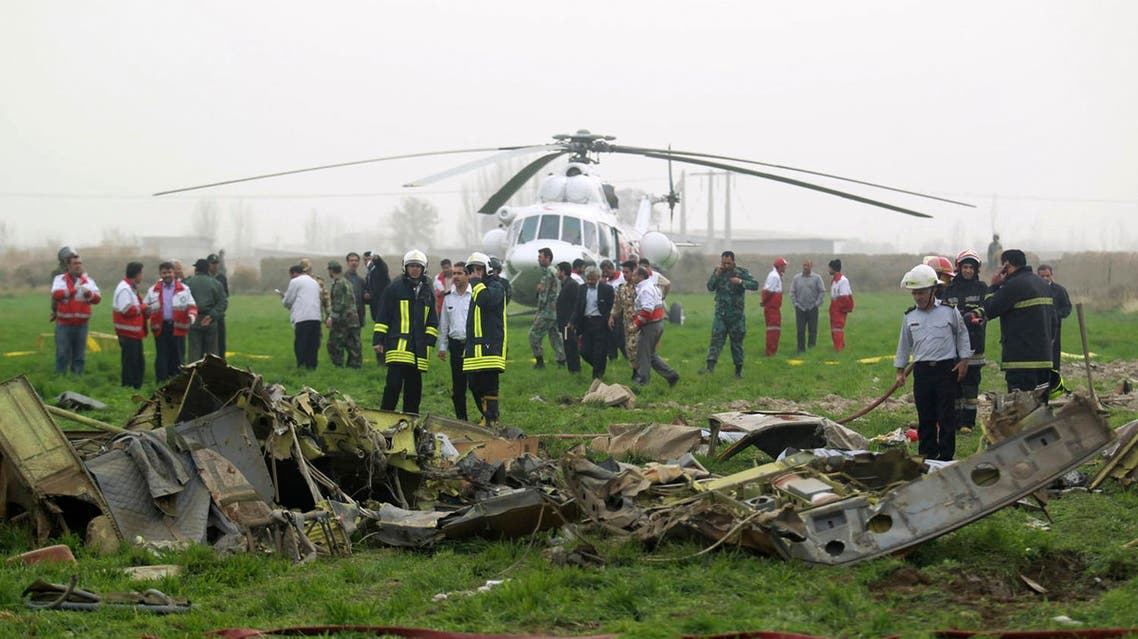 Rescuers and officials work at the scene of a helicopter crash, just outside the city of Mashhad, northeastern Iran, on Wednesday, Nov. 14, 2012. AP