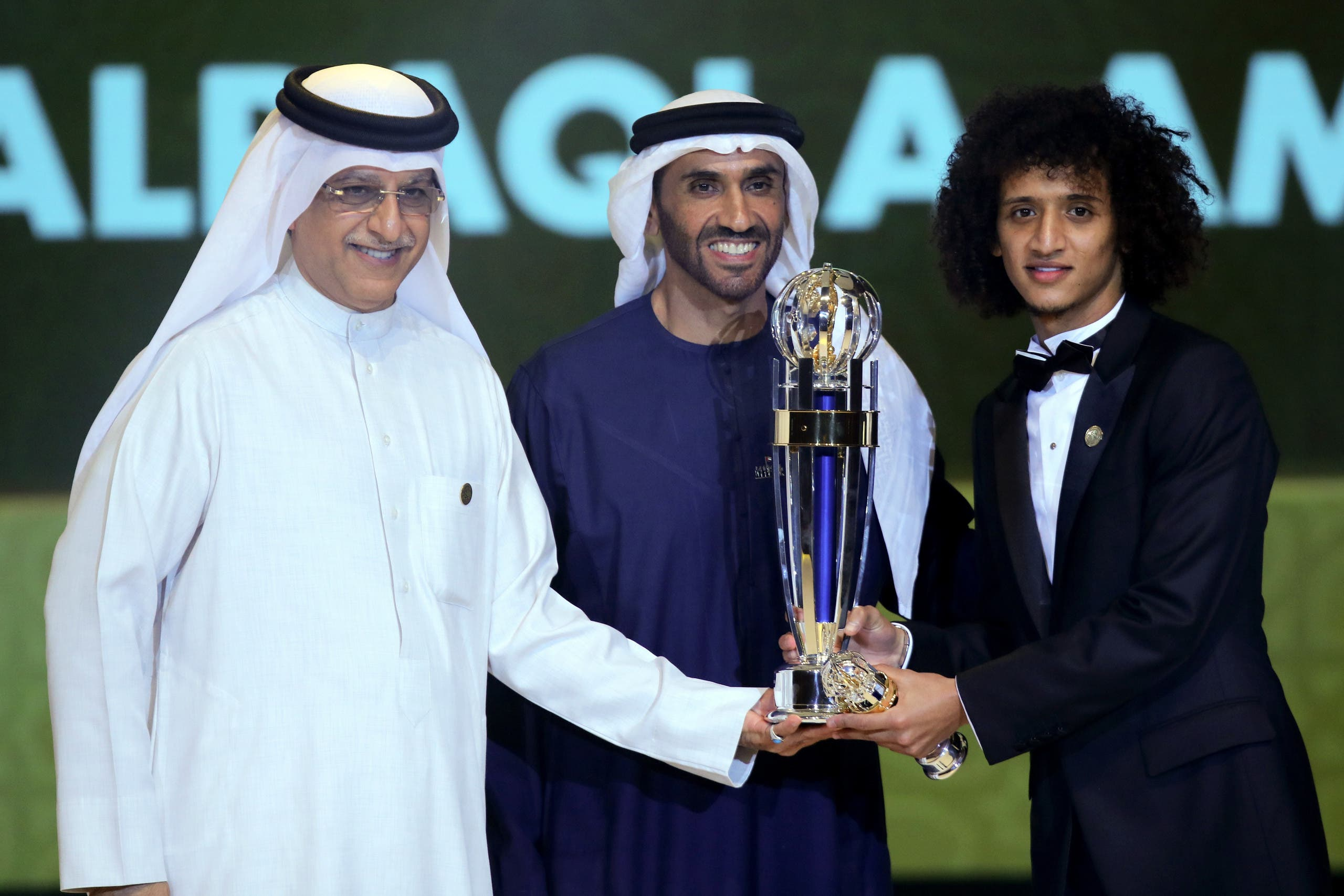 Shaikh Salman bin Ebrahim Al Khalifa (L), President of the Asian Football Confederation (AFC), and Sheikh Nahyan Bin Zayed Al Nahyan (C), Chairman of the Abu Dhabi Sports Council, present Omar Abdulrahman (R) with a trophy after being named the AFC Men's Footballer of the Year during the Asian Football Confederation's Annual Awards ceremony on December 1, 2016 in Abu Dhabi.  NEZAR BALOUT / AFP