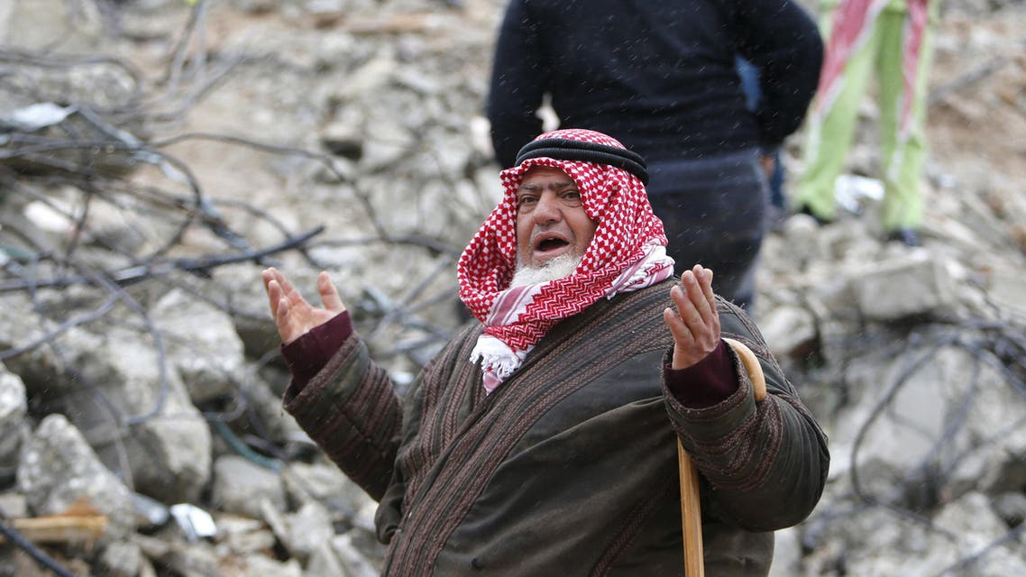 A Palestinian man gestures as he talks to the media on the rubble of of Palestinian Raed Masalmeh's home after it was demolished by Israeli army in the West Bank town of Dura, south of Hebron February 23, 2016. reuters