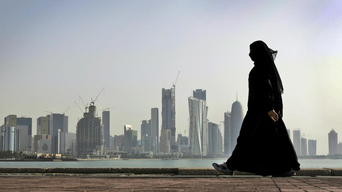 In this May 14, 2010 file photo, a Qatari woman walks in front of the city skyline in Doha, Qatar. ap