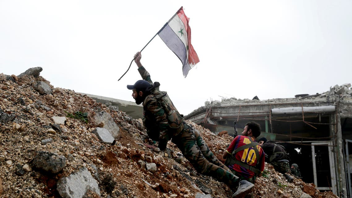A Syrian army soldier places a Syrian national flag during a battle with rebel fighters at the Ramouseh front line, east of Aleppo, Syria, Monday, Dec. 5, 2016. The government seized large swathes of the Aleppo enclave under rebel control since 2012 in the offensive that began last week. The fighting was most intense Monday near the dividing line between east and west Aleppo as government and allied troops push their way from the eastern flank, reaching within less than a kilometer (half a mile) from the citadel that anchors the center of the city. (AP Photo/Hassan Ammar)