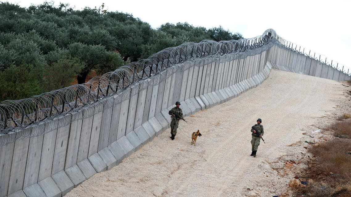 A K9 unit patrol along a wall on the border line between Turkey and Syria, near the southeastern village of Besarslan, in Hatay province, Turkey, November 1, 2016
