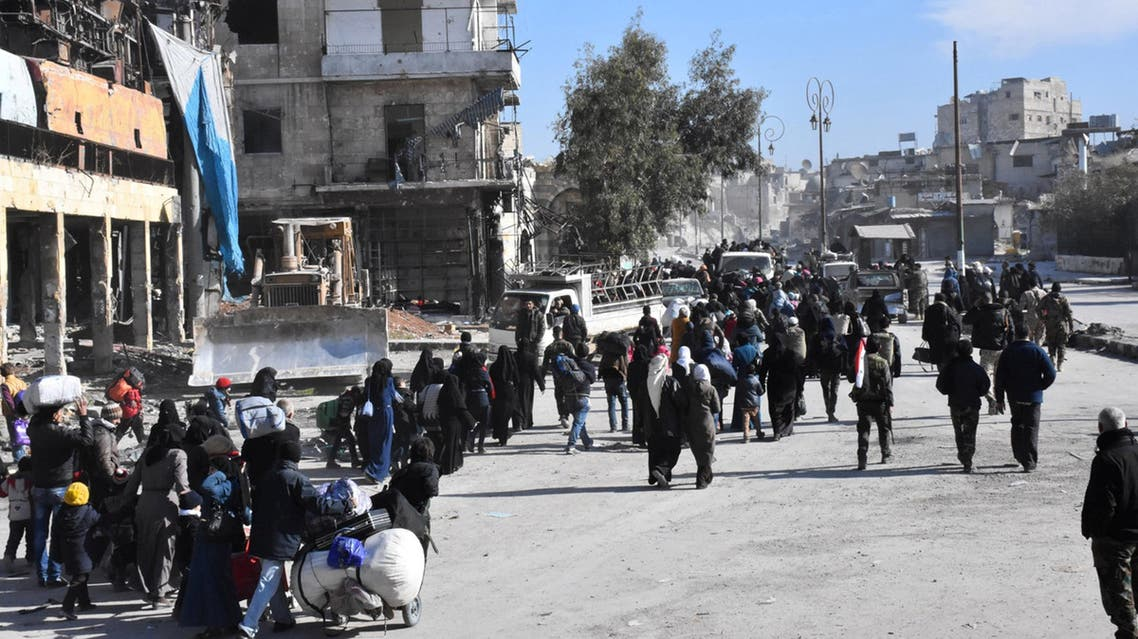 People, who left the eastern districts of Aleppo, carry their belongings as they walk in a government held area of Aleppo
