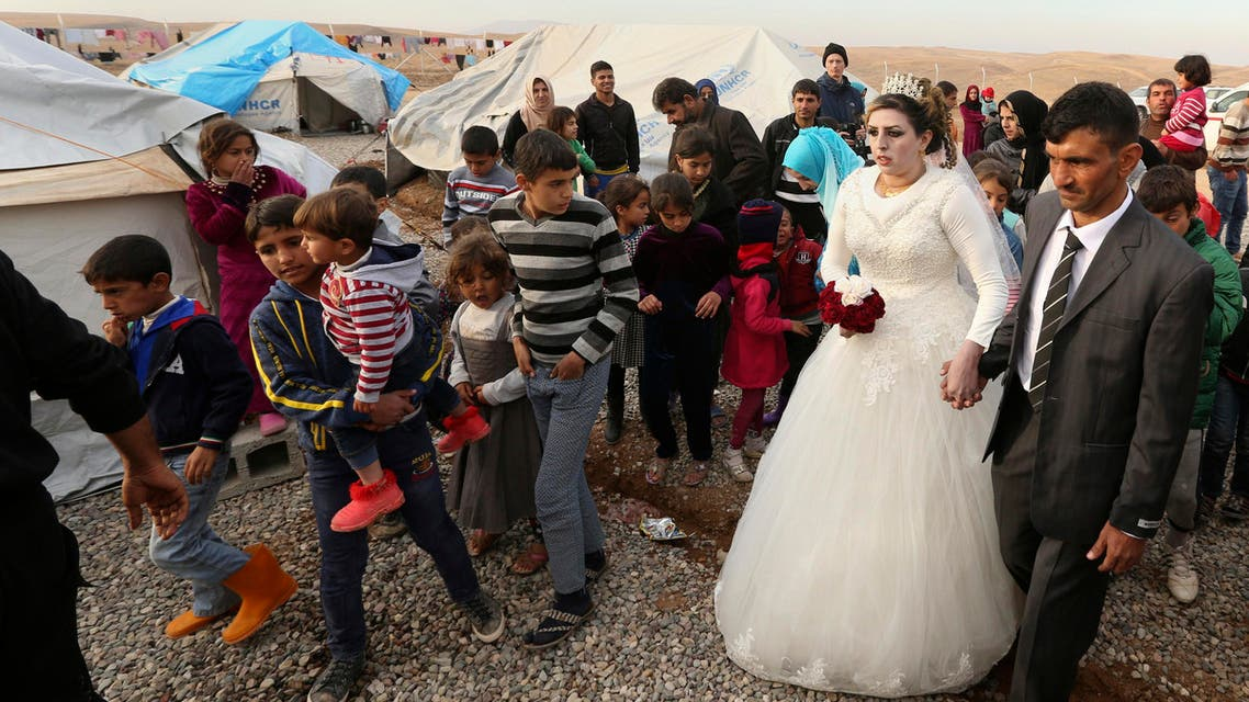 Iraqi internally displaced groom Jassim Mohammed walks with his bride, Amena Ali, during their wedding ceremony at a camp for internally displaced people, in Khazir, near Mosul, Iraq, Thursday, Dec. 8, 2016. (AP)