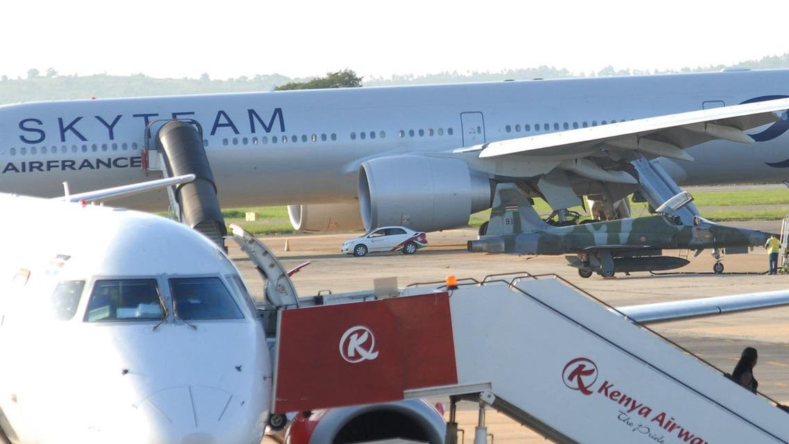 In this photo of Sunday, Dec. 20, 2015, A Kenyan military jet parked next to AirFrance plane, background, which made emergency landing at Moi International Airport on Saturday, in Mombasa, Kenya, Sunday, Dec. 20, 2015. A retired French police officer traveling on Air France was detained Monday after a fake bomb hidden in a lavatory forced his Paris-bound flight to make an emergency landing in Kenya, according to prosecutors. The hoax, the fourth against Air France in recent weeks, comes amid heightened concerns about extremist violence in many countries, and aggravated passenger jitters around the holidays.(AP Photo)  Use Information This content is intended for editorial u