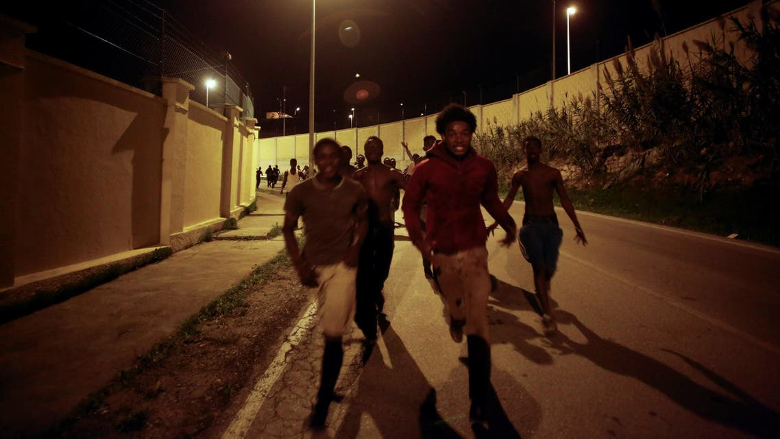 African migrants run down a road after crossing the border fence between Morocco and Spain's north African enclave of Ceuta, December 9, 2016