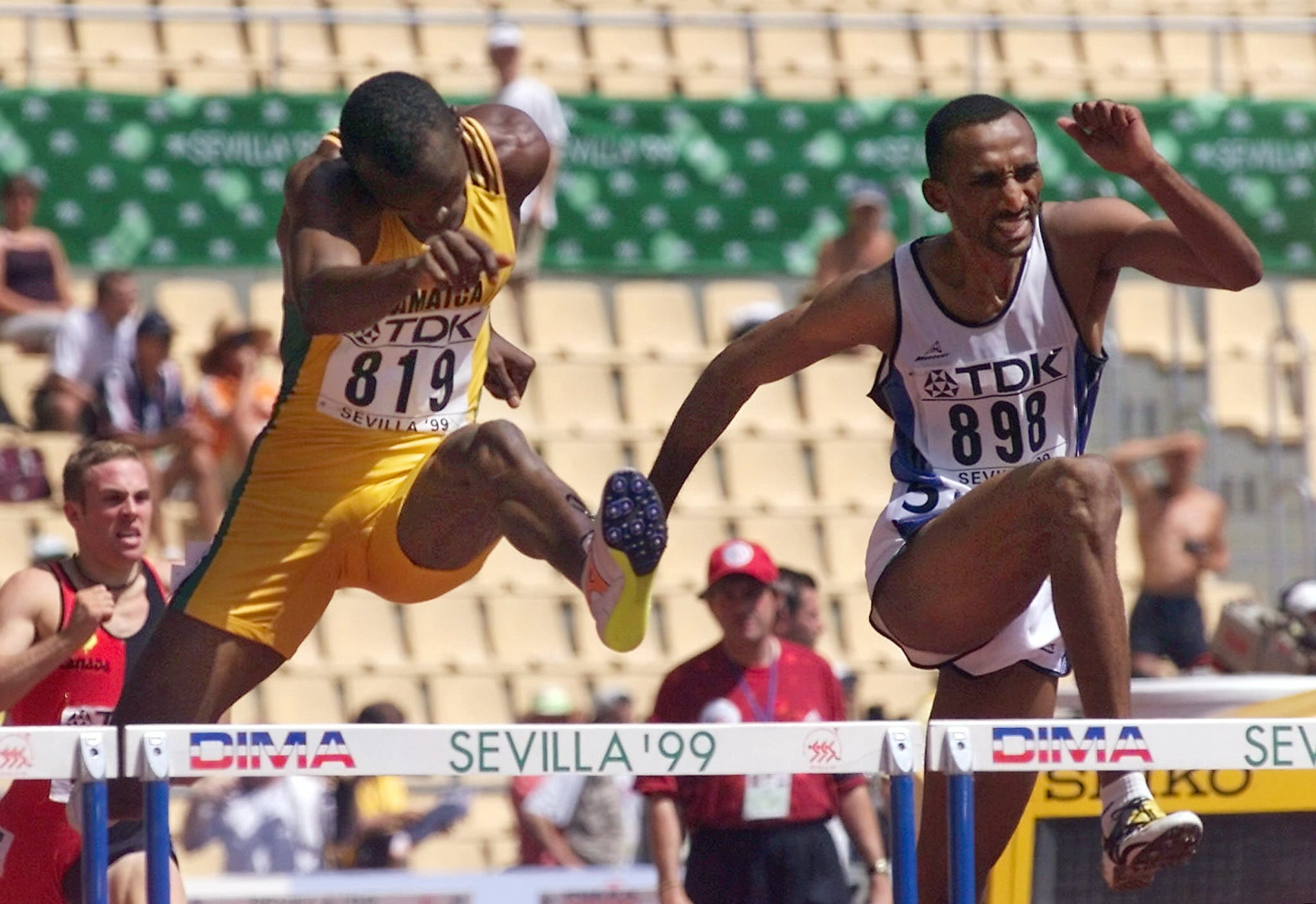 Jamaica's Dinsdale Morgan (L) and Saudi Hadi Soua'an al-Somaily clear a hurdle in heat 4 of the men's 400m hurdles competition at the World Athletics Championships in Seville 24 August 1999. (AFP)