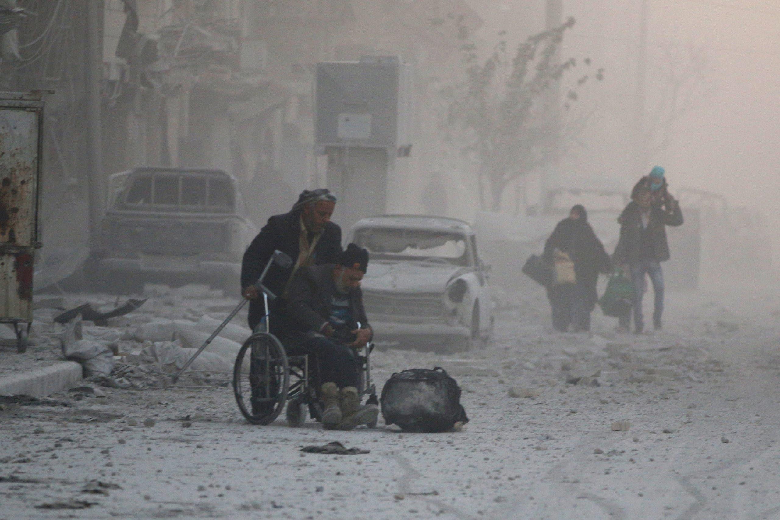 رجل على كرسي متحرك يهرب مع آخرين من القصف داخل حلب الشرقية