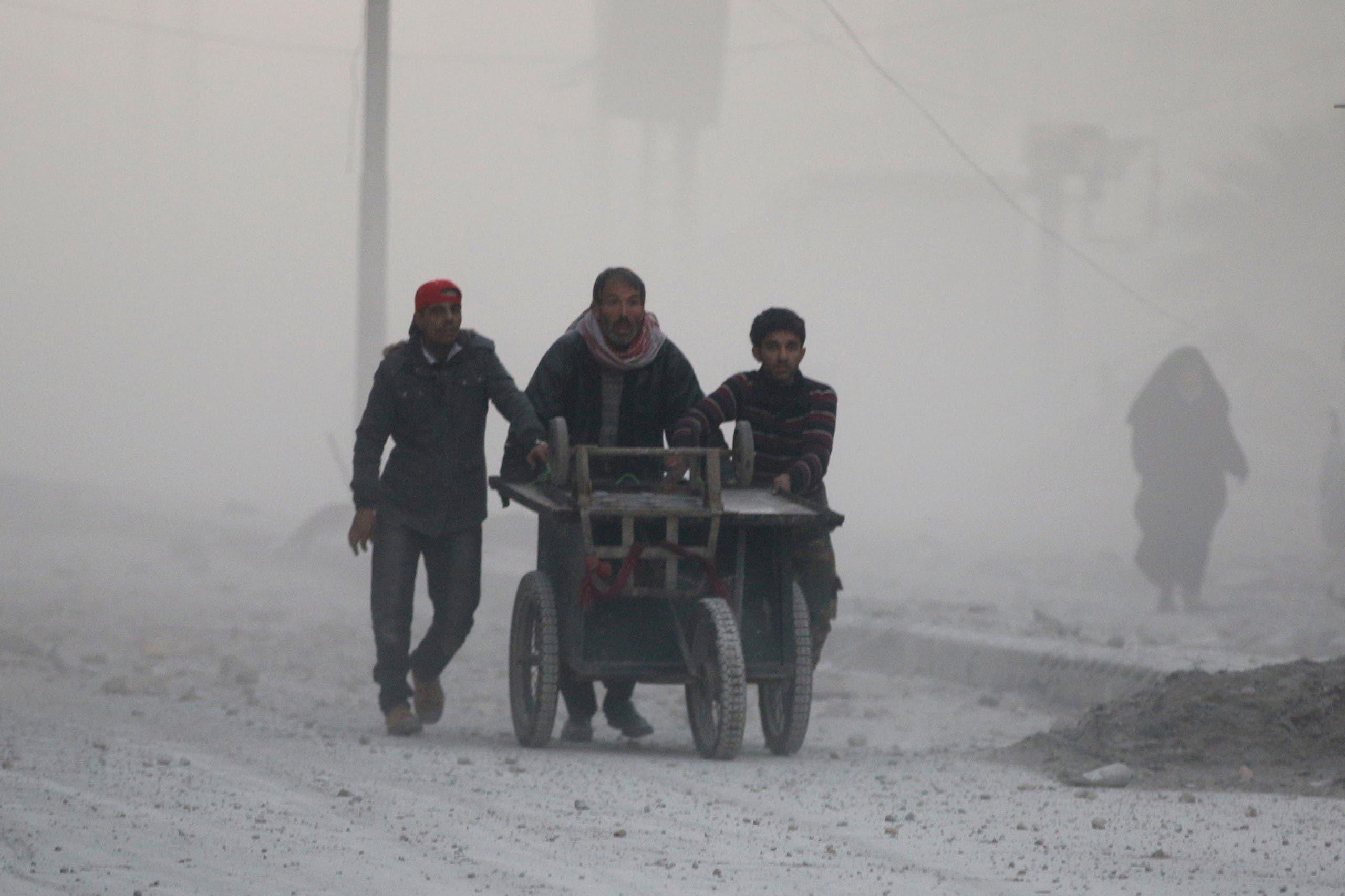 رجال يجرون عربة خلال هروبهم ودخولهم في عمق مناطق سيطرة المعارضة في شرق حلب