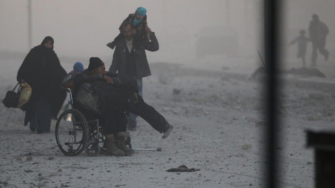 A man on a wheelchair flees with others into the remaining rebel-held areas of Aleppo Syria December 9, 2016