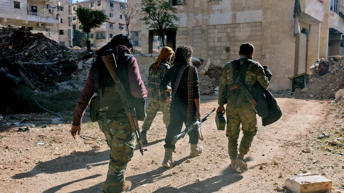 Rebel fighters walk down a street west of the northern Syrian city of Aleppo on December 9, 2016