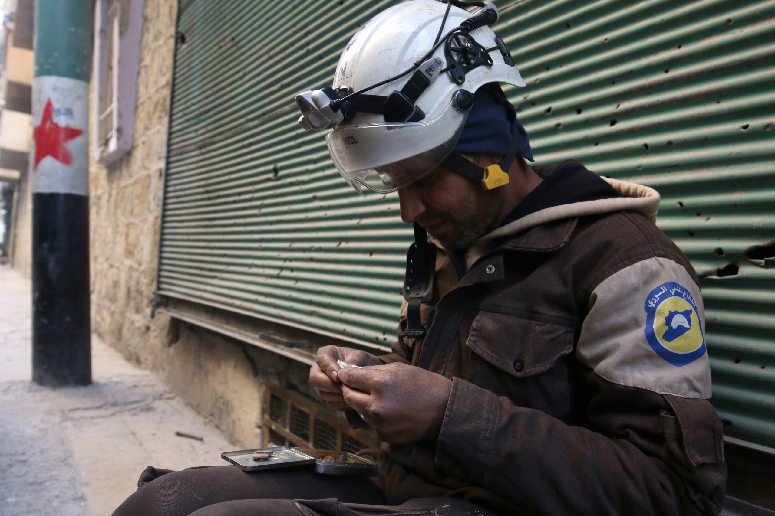 عنصر من الدفاع المدني يستريح ويدخن سيجارة في شرق حلب