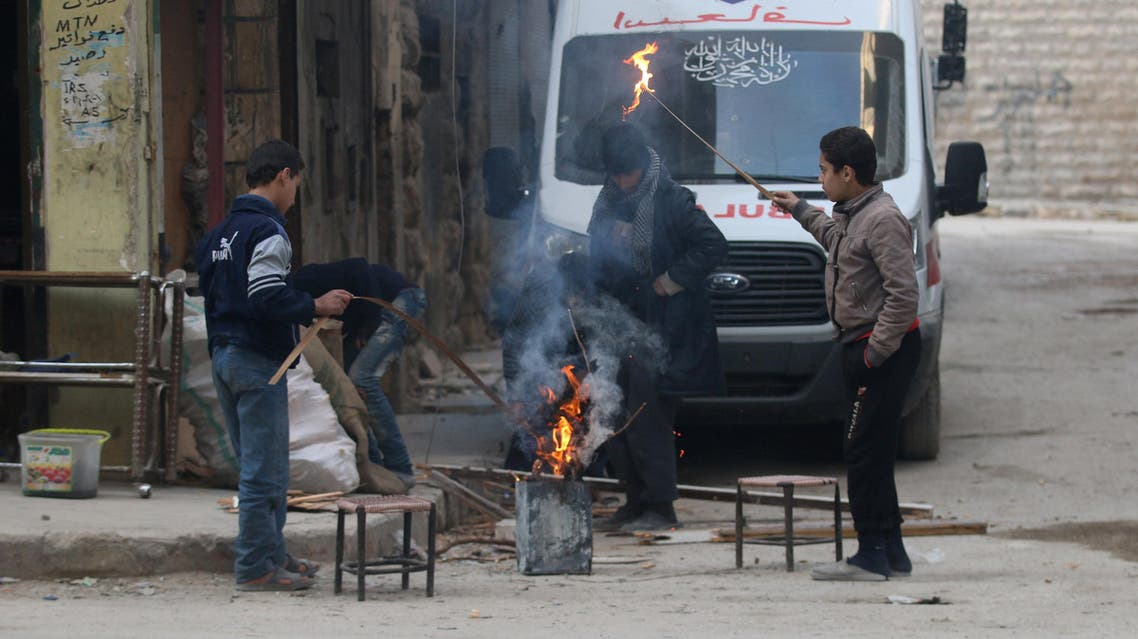 People warm themselves around a fire in a rebel-held area of Aleppo, Syria December 8, 2016