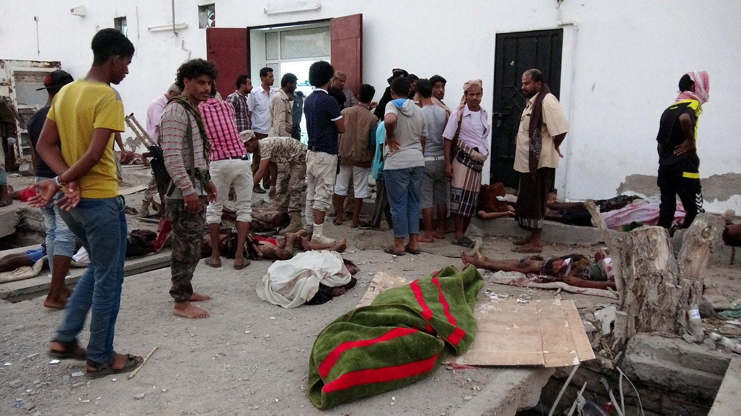 Soldiers and people gather by the bodies of soldiers killed by a suicide bomber at a base in the southern port city of Aden. (Reuters)