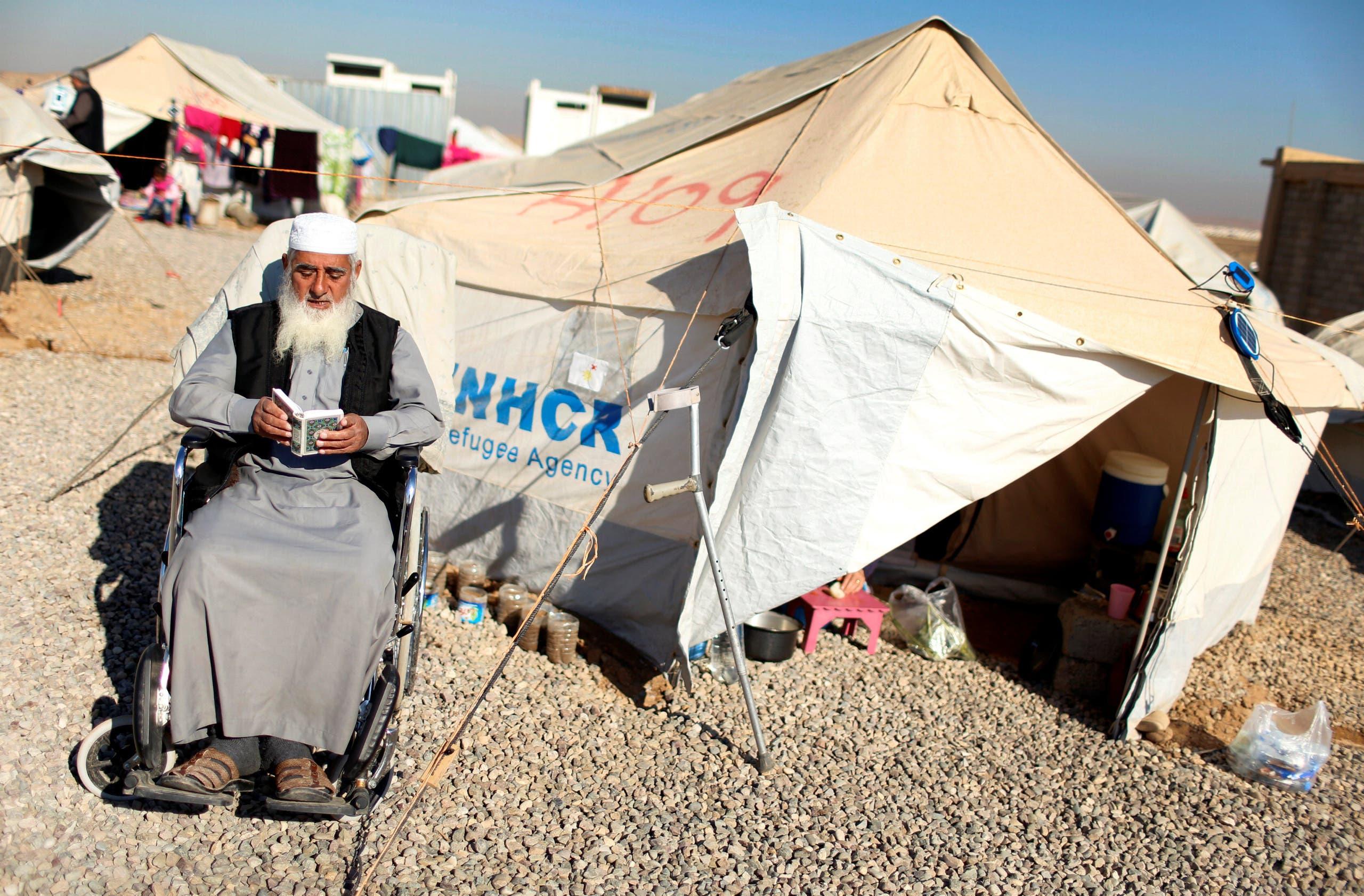 مسن عراقي يقرأ القرآن قرب خيمة في مخيم لنازحي الموصل