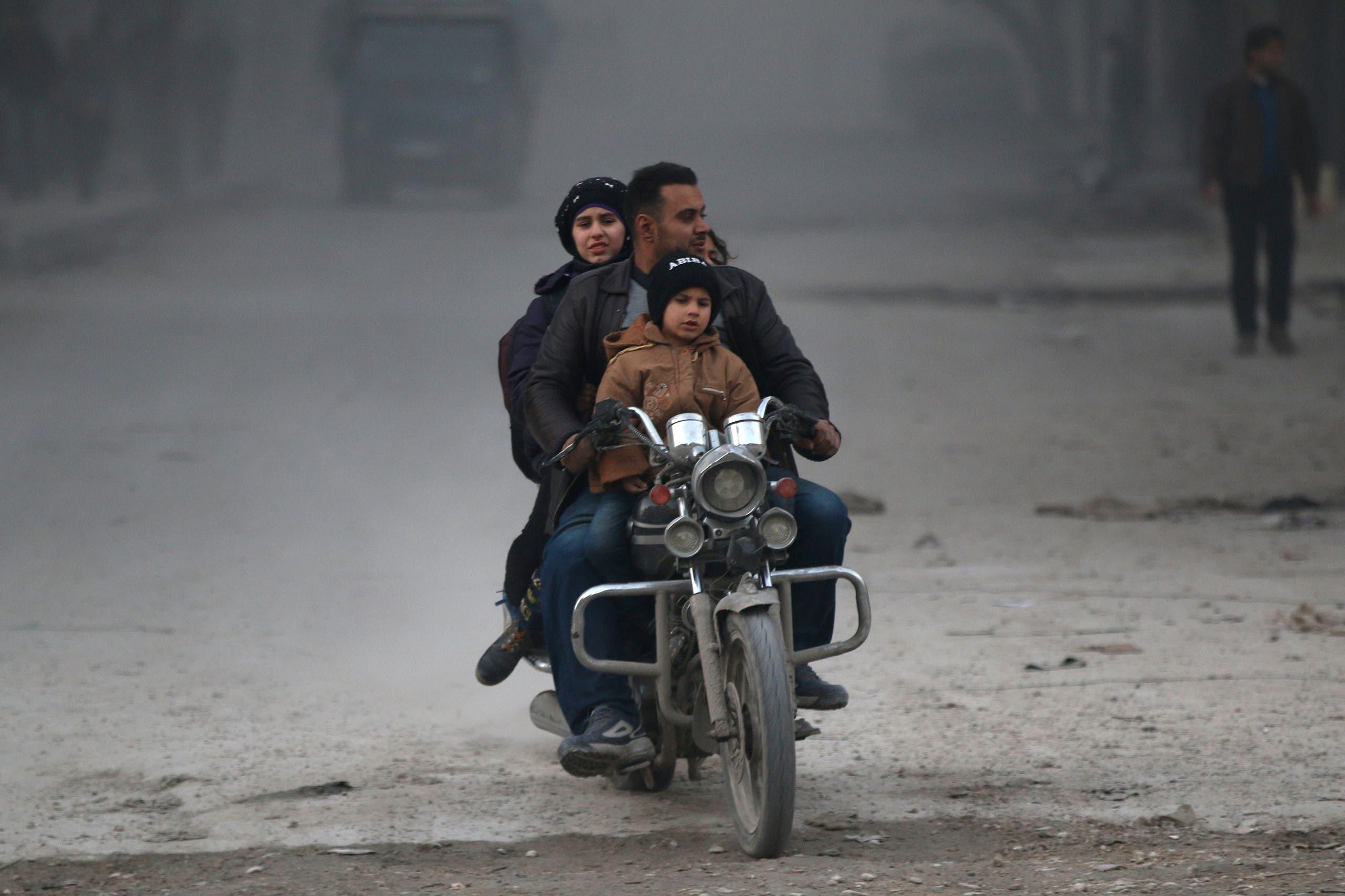 مدنيون يستقلون دراجة نارية للهروب والدخول في عمق مناطق سيطرة المعارضة في حلب الشرقية