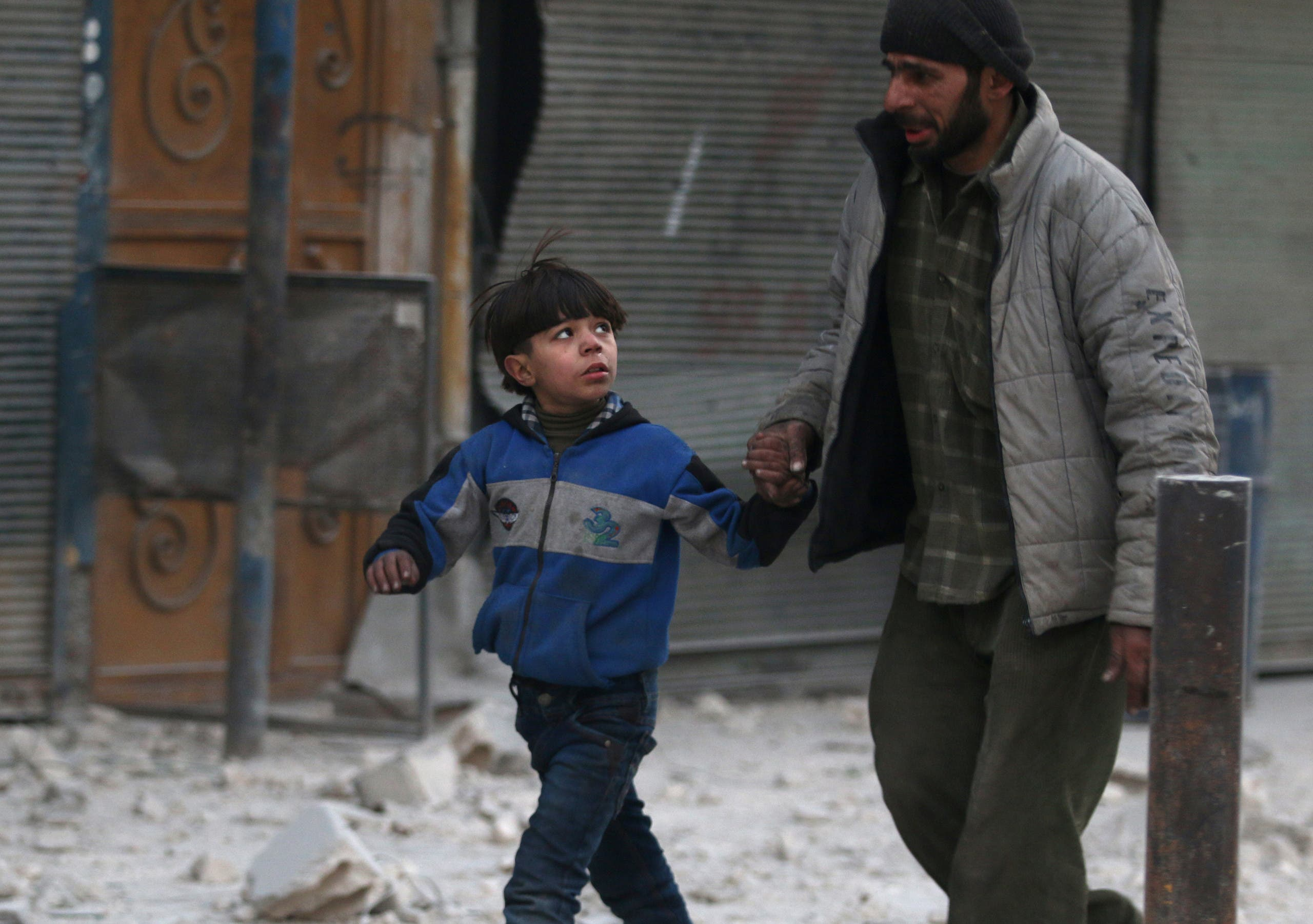 A man holds the hand of a boy as they flee deeper into the remaining rebel-held areas of Aleppo, Syria December 9, 2016