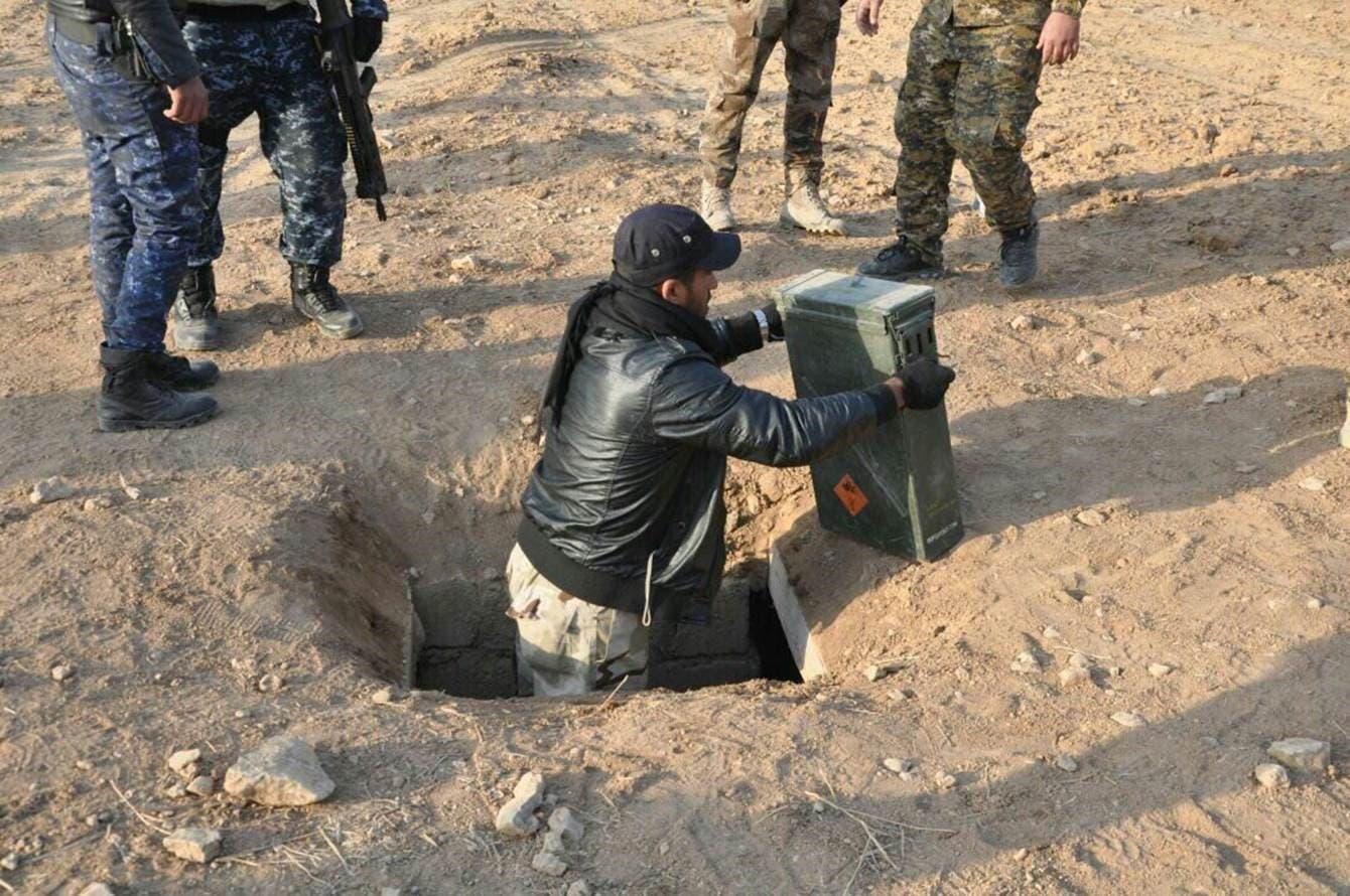 جندي عراقي يقوم بإخراج صناديق أسلحة لداعش وضعت في نفق تحت الأرض في الموصل