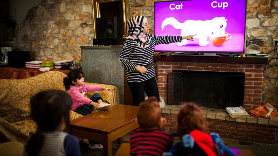 Manar, a Syrian refugee who fled home with her three children, teaches English to a group of young children. © UNHCR/Achilleas Zavallis
