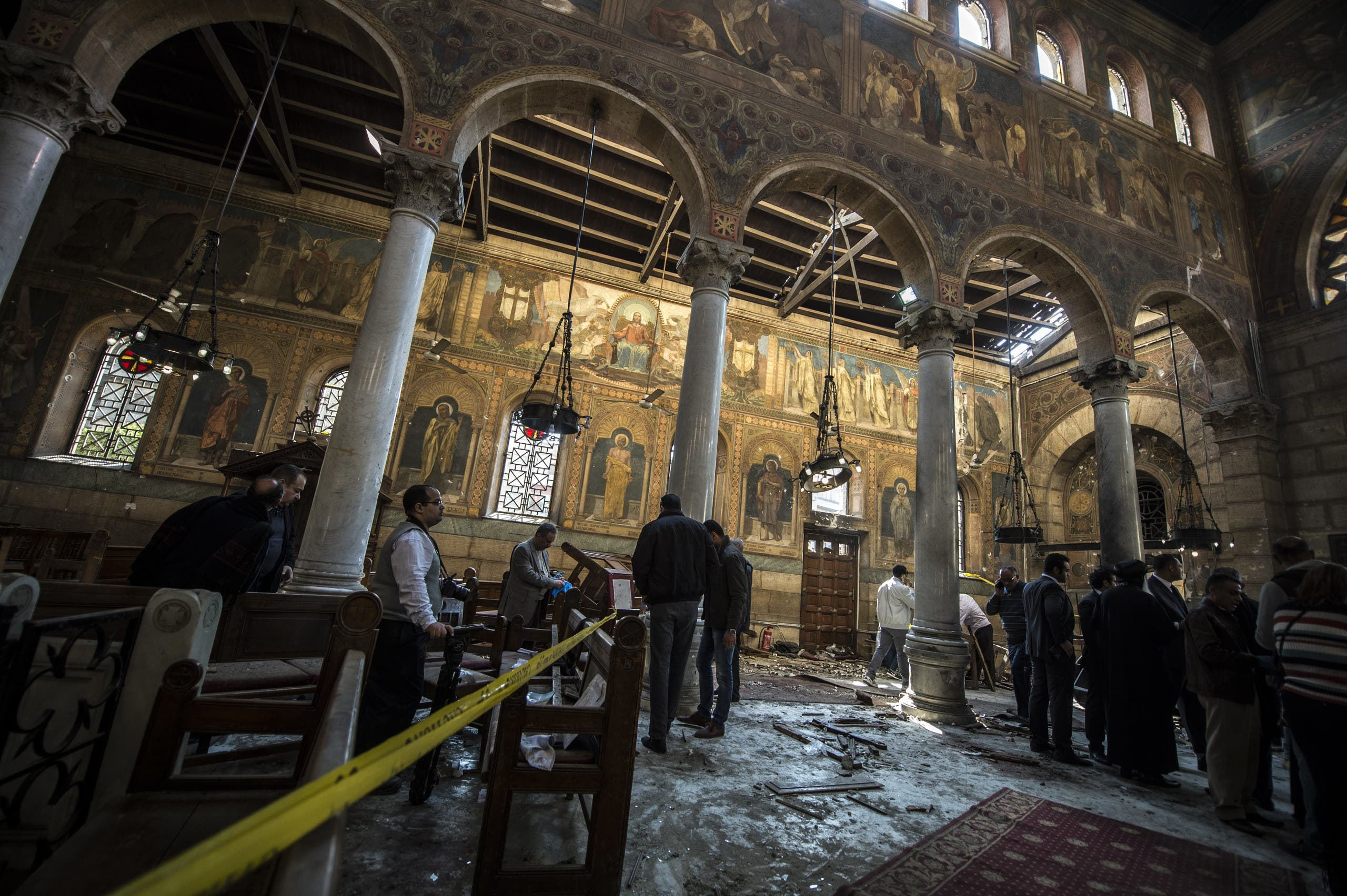 Egyptian security forces and members of the clergy inspect the scene of a bomb explosion at the Saint Peter and Saint Paul Coptic Orthodox Church on December 11, 2016, in Cairo's Abbasiya neighbourhood. AFP