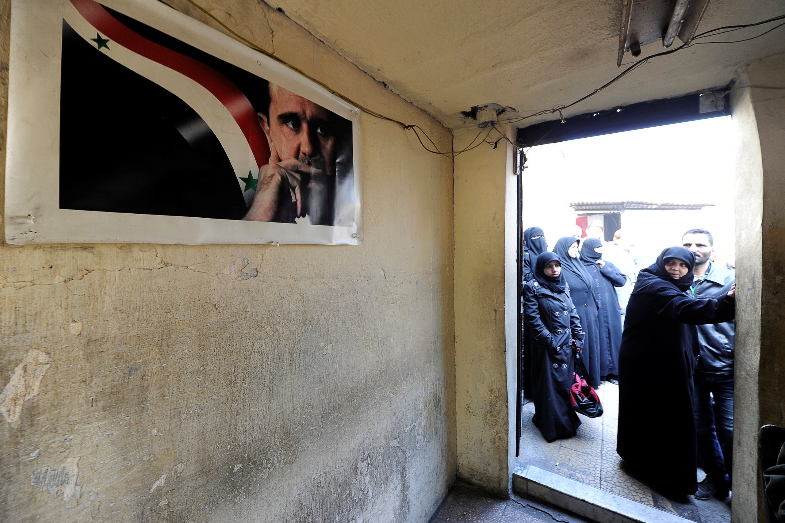 Civilians wait outside a government military police centre to visit their relatives, who were evacuated from the eastern districts of Aleppo and are being prepared to begin their military service, in Aleppo, Syria December 11, 2016.