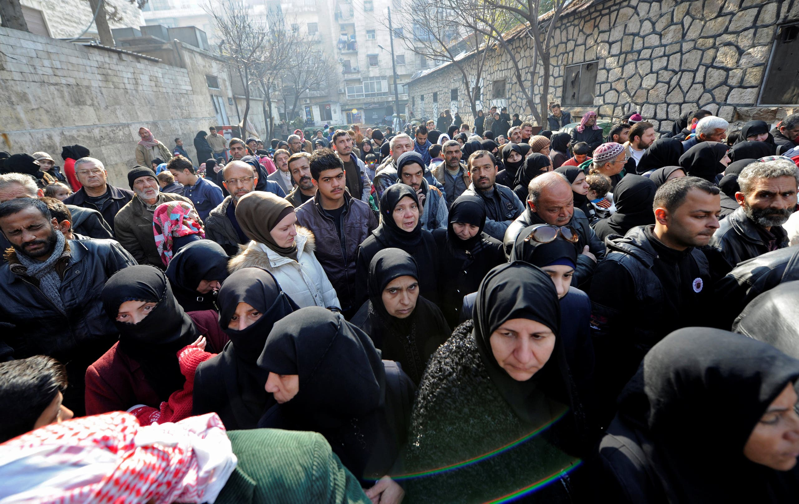 Civilians wait outside a government military police centre to visit their relatives, who were evacuated from the eastern districts of Aleppo and are being prepared to begin their military service, in Aleppo, Syria December 11, 2016. (Reuters)