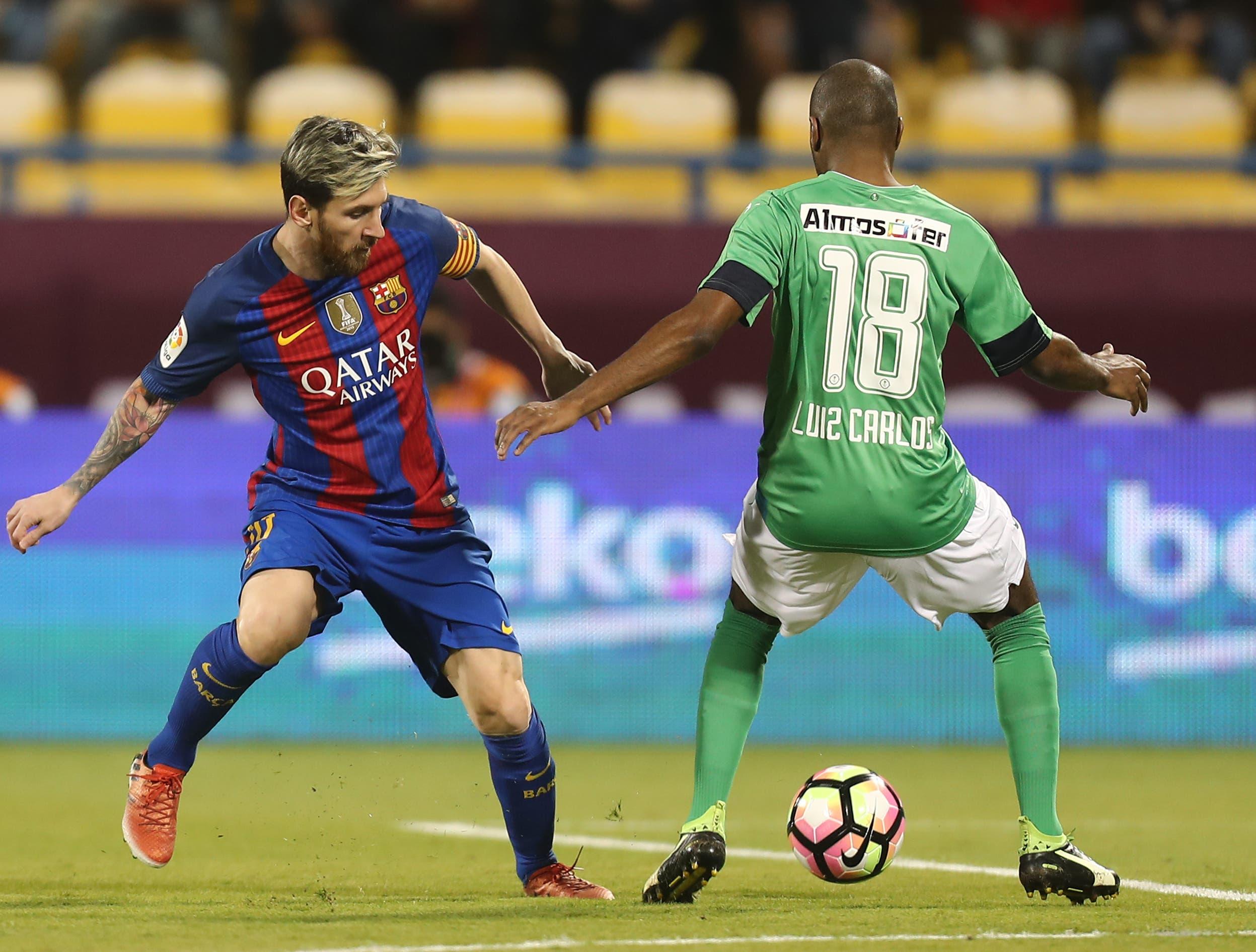 FC Barcelona's Lionel Messi (L) vies with Al-Ahli's Luiz Carlos during a friendly football match between FC Barcelona and Saudi Arabia's Al-Ahli FC on December 13, 2016 in the Qatari capital Doha. (AFP)