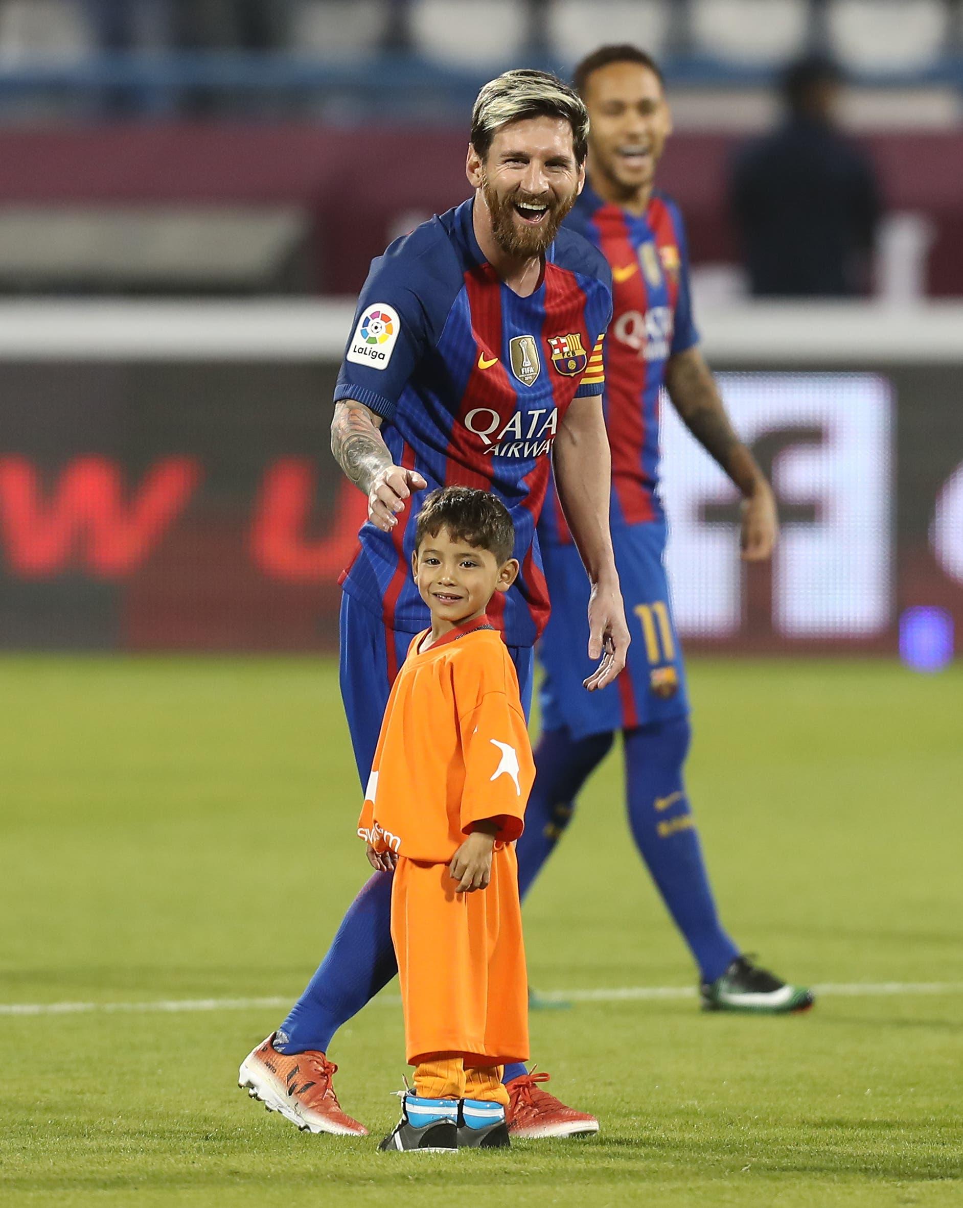 FC Barcelona Lionel Messi talks to Afghan boy Murtaza Ahmadi on the pitch before the start of a friendly football match against Saudi Arabia's Al-Ahli FC on December 13, 2016 in the Qatari capital Doha. (AFP)