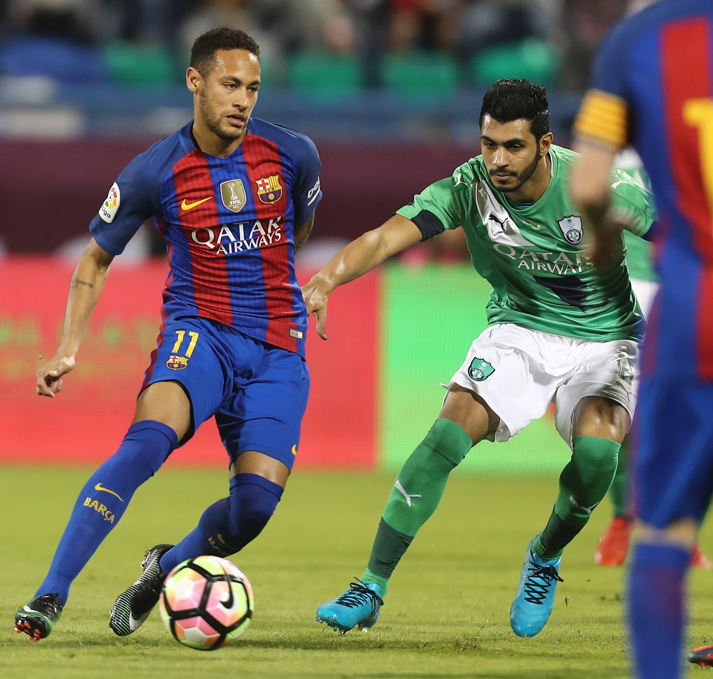 FC Barcelona's Neymar (L) vies with Al-Ahli's Mohammed al-Fatil during a friendly football match between FC Barcelona and Saudi Arabia's Al-Ahli FC on December 13, 2016 in the Qatari capital Doha. (AFP)