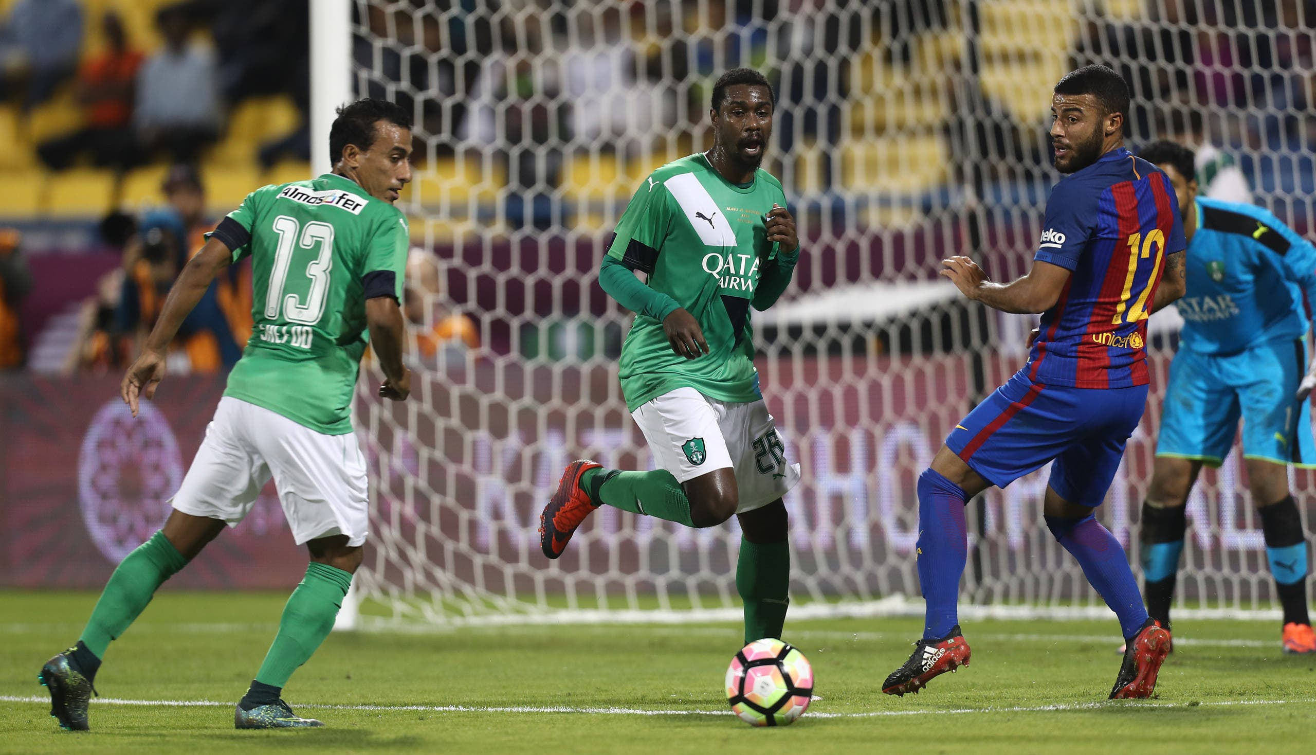 FC Barcelona's Rafinha vies for the ball with Al-Ahly's Mohamed Abdel Shafy and Mohamed Aman during a friendly football match between FC Barcelona and Saudi Arabia's Al-Ahli FC on December 13, 2016 in the Qatari capital Doha. (AFP)
