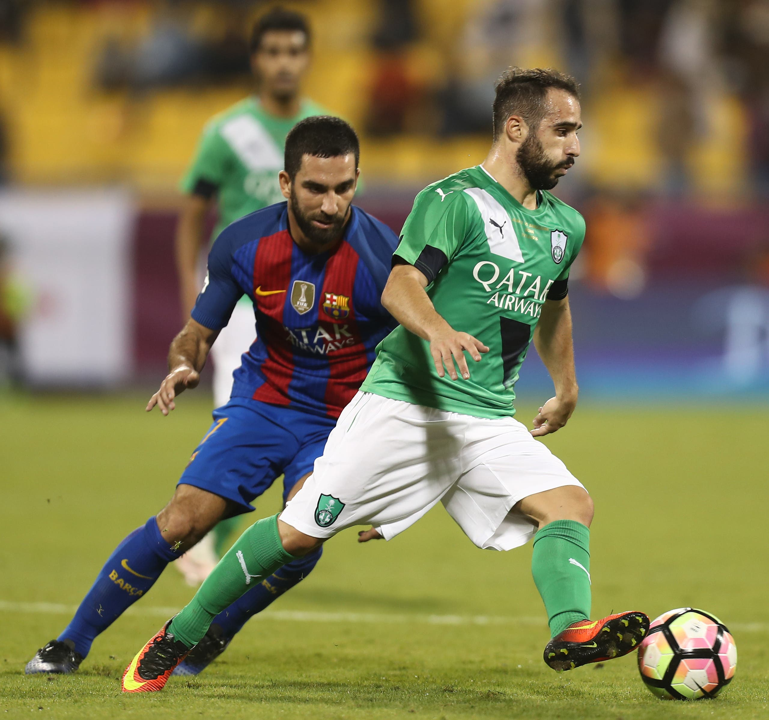 FC Barcelona's Arda Turan (L) vies for the ball with Al-Ahly's Giannis Fetfatzidis during a friendly football match between FC Barcelona and Saudi Arabia's Al-Ahli FC on December 13, 2016 in the Qatari capital Doha. (AFP)