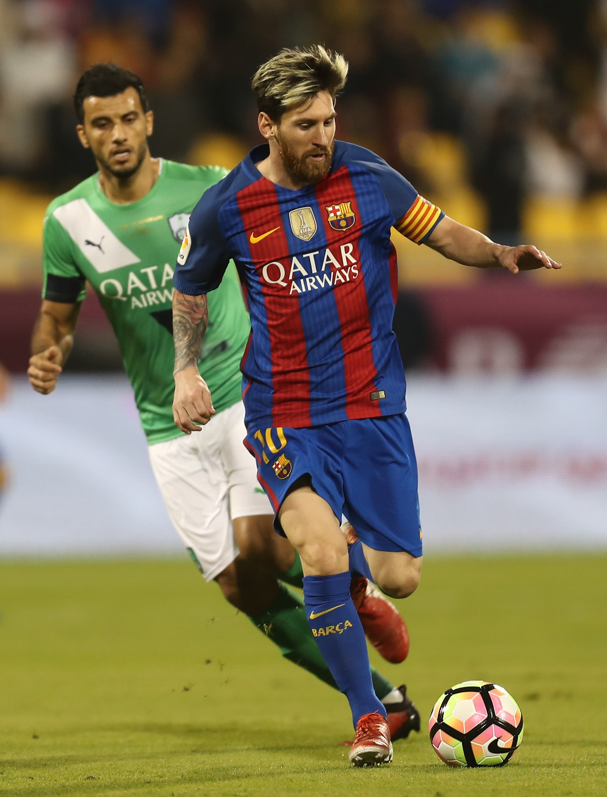 FC Barcelona's Lionel Messi (R) vies with a player of Al-Ahli during a friendly football match between FC Barcelona and Saudi Arabia's Al-Ahli FC on December 13, 2016 in the Qatari capital Doha. (AFP)