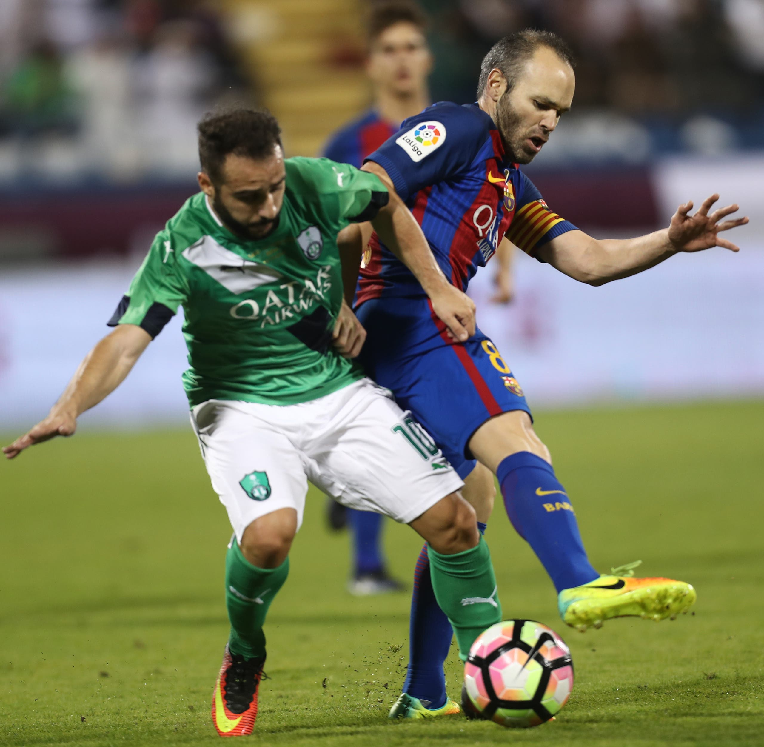 FC Barcelona's Andres Iniesta vies for the ball with Al-Ahly's Giannis Fetfatzidis during a friendly football match between FC Barcelona and Saudi Arabia's Al-Ahli FC on December 13, 2016 in the Qatari capital Doha. (AFP)