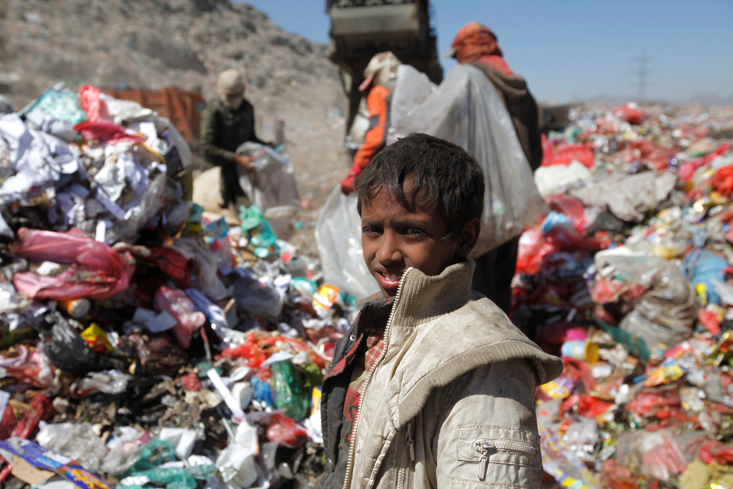 A girl sits on a pile of rubbish at landfill site on the outskirts of Sanaa, Yemen November 16, 2016.
