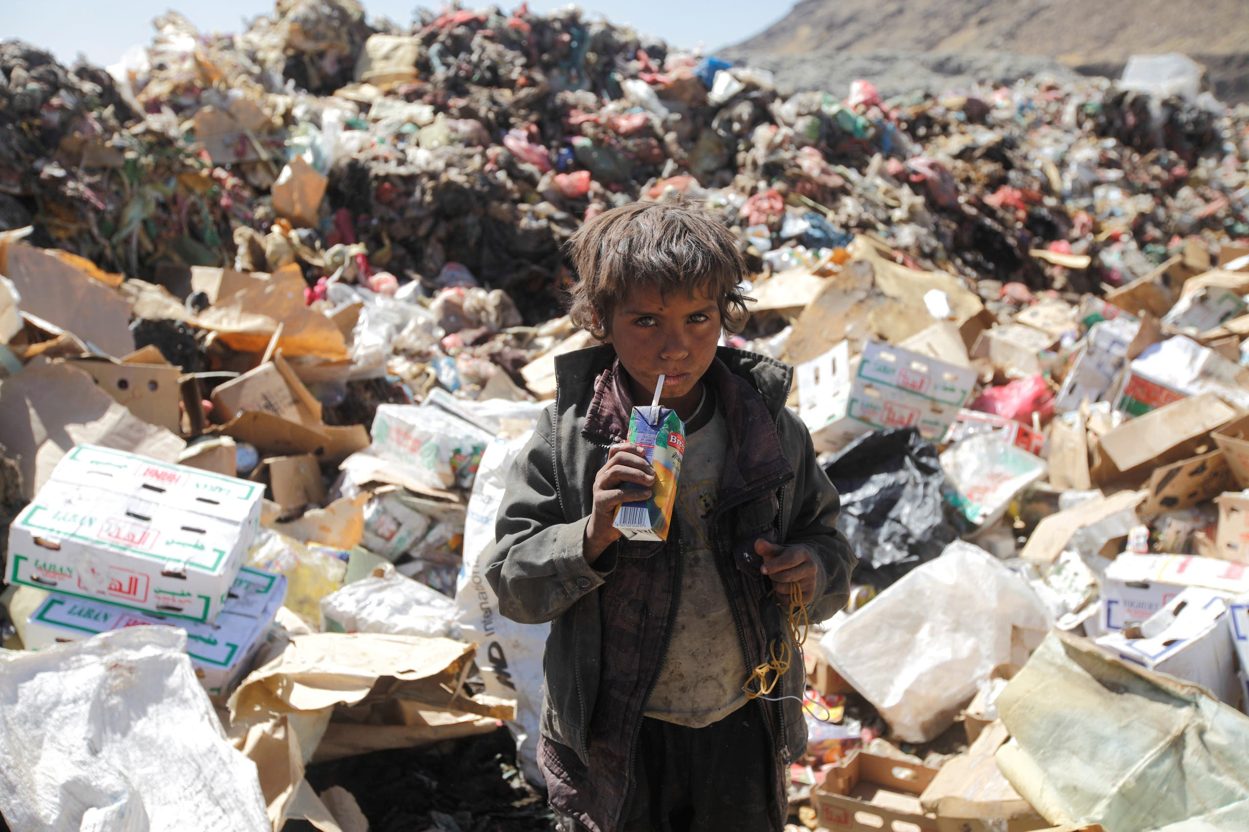 A boy drinks expired juice on a pile of rubbish at landfill site on the outskirts of Sanaa, Yemen November 16, 2016. (Reuters)