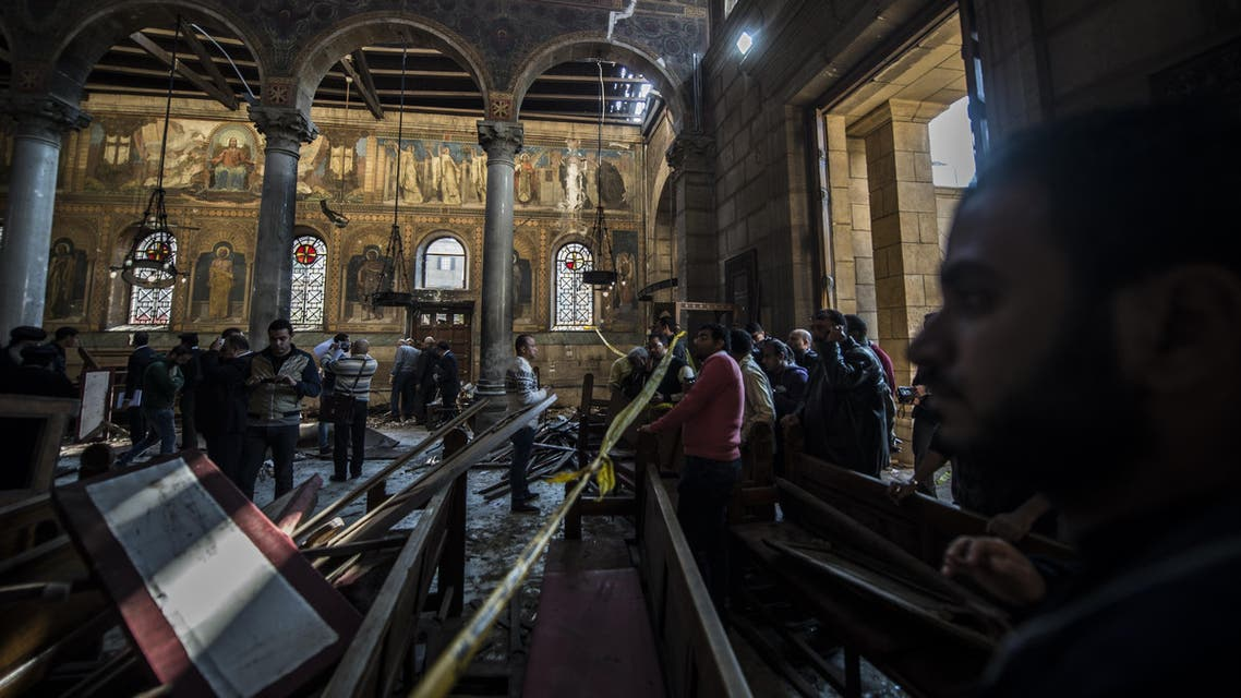 Egyptian security forces (L) inspect the scene of a bomb explosion at the Saint Peter and Saint Paul Coptic Orthodox Church on December 11, 2016, in Cairo's Abbasiya neighbourhood. The blast killed at least 25 worshippers during Sunday mass inside the Cairo church near the seat of the Coptic pope who heads Egypt's Christian minority, state media said. KHALED DESOUKI / AFP