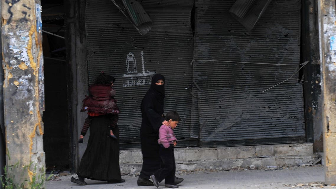 Syrian women walk with their children in the northern Syrian city of Aleppo on March 23, 2013. In Aleppo, nine months into fighting that has devastated many districts, life has slowly started to return to what passes for normal in Syria today. AFP
