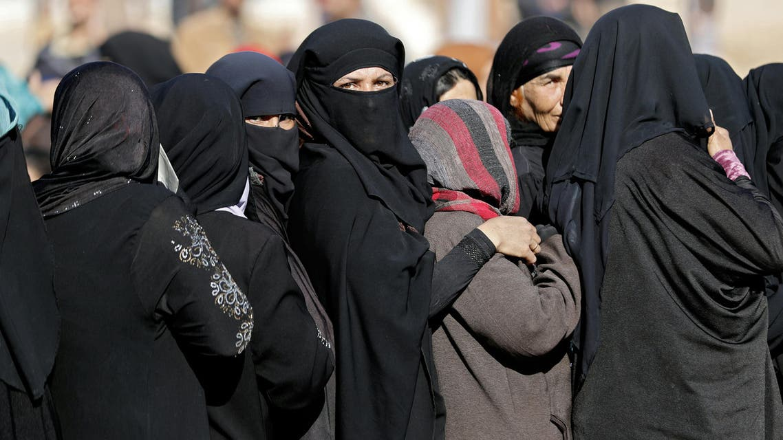 Displaced Iraqi women queue to receive food distribution from a British charity, on December 4, 2016 in the village of Gogjali, on the eastern edge of Mosul, as Iraqi forces continue to battle against Islamic State (IS) group jihadists. Tens of thousands of Iraqi forces launched a massive operation to retake Mosul, the jihadists' last major bastion in Iraq, on October 17.