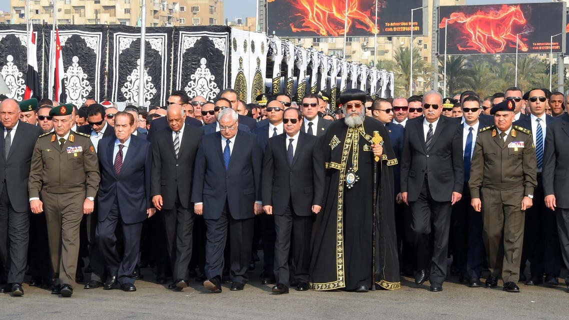 A handout picture released by the Egyptian Presidency on December 12, 2016, shows President Abdel Fattah al-Sisi (C), Coptic Pope Tawadros II (C-R) walking alongside other officials during the funeral of the victims of a bomb explosion that targeted a Coptic Orthodox Church the previous day in Cairo. (AFP)