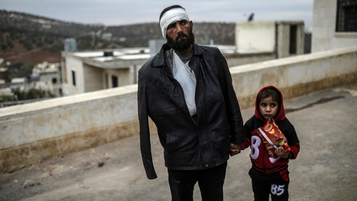 "An injured Syrian man who just arrived on the Syrian side of the Bab al-Hawa border crossing between Syria and Turkey waits with his child outside a hospital on December 16, 2016. The Syrian government suspended the evacuation of the last rebel-held parts of Aleppo, but a military source denied a Russian statement that the operation was ""complete."" (AFP)"