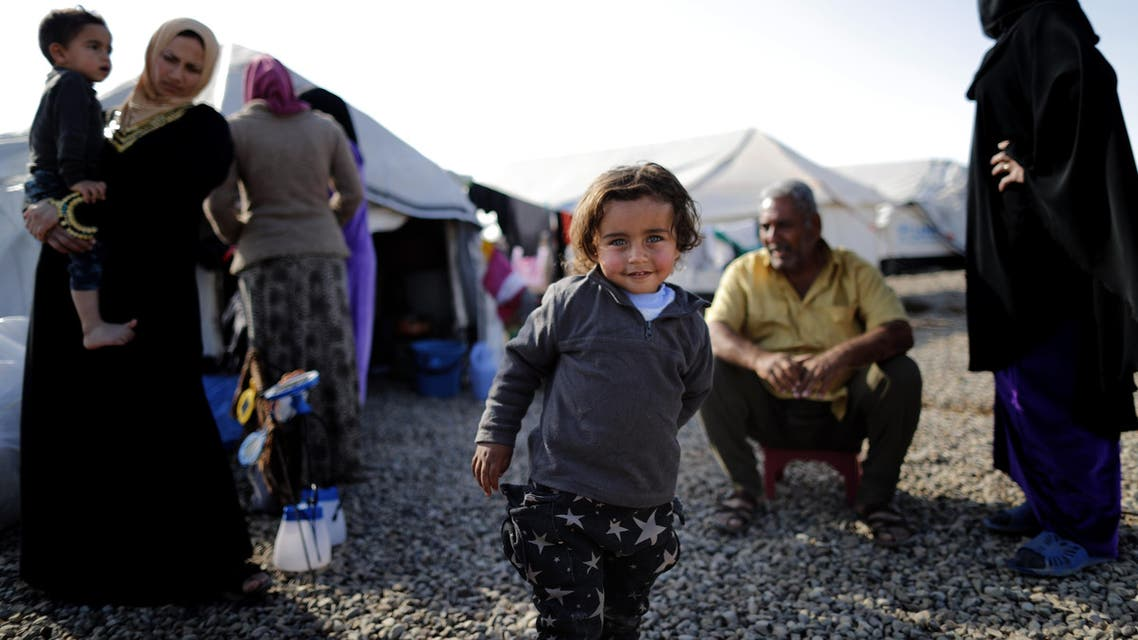 This file photo taken on December 3, 2016 shows a displaced Iraqi boy, who fled the violence in the Iraqi northern city of Mosul as a result of a planned operation to retake the city from jihadists, posing at Hasan Sham refugee camp, some 30 kilometres east of Mosul.