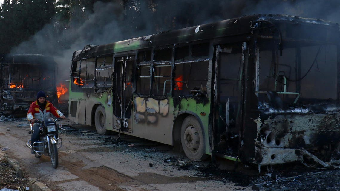 A man on a motorcycle drives past burning buses while en route to evacuate ill and injured people from the besieged Syrian villages of al-Foua and Kefraya, after they were attacked and burned, in Idlib province, Syria December 18, 2016. (Reutetrs)