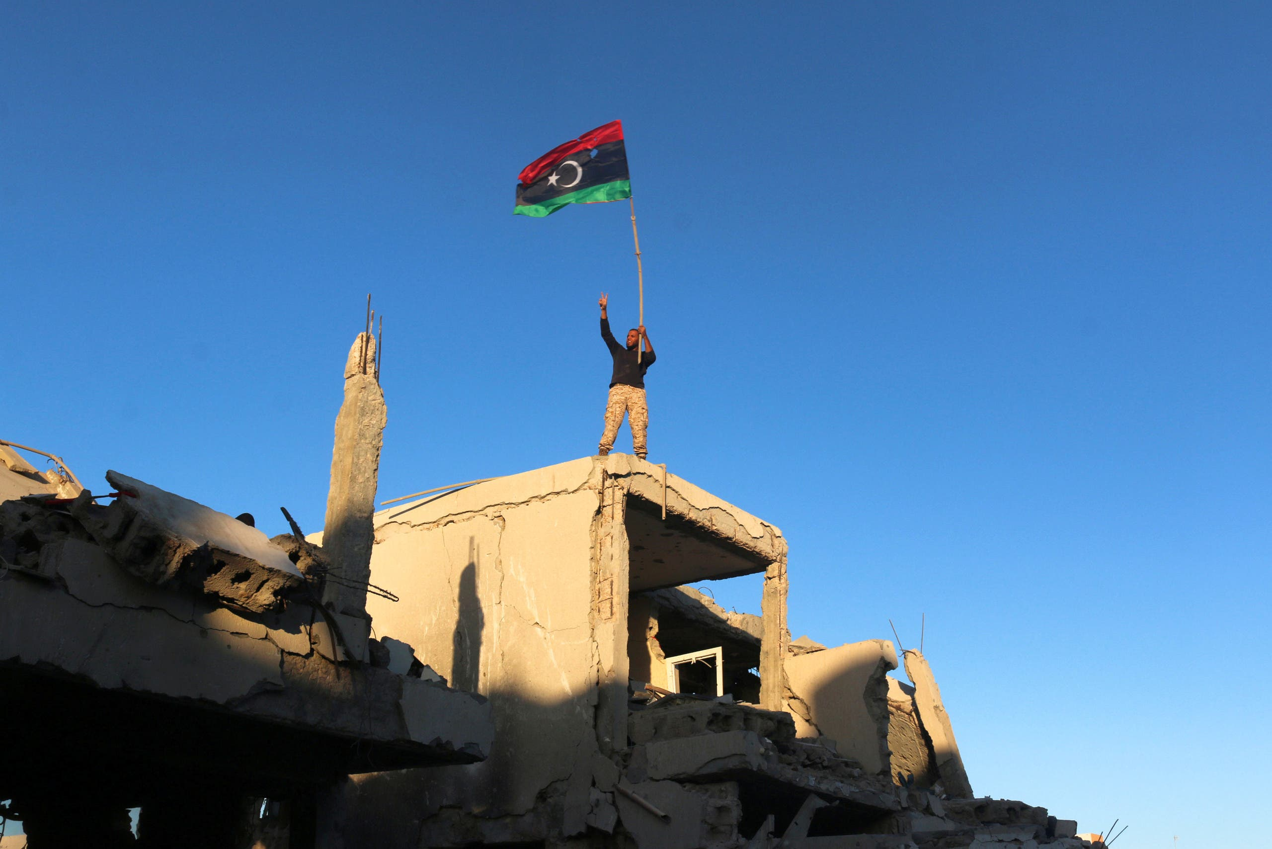 A fighter of Libyan forces allied with the UN-backed government waving a Libyan flag flashes victory sign as he stands atop the ruins of a house after forces finished clearing Ghiza Bahriya, the final district of the former ISIS stronghold of Sirte, Libya. (Reuters)