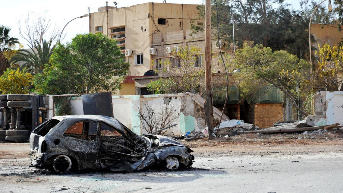 In this March 10, 2016 file photo, damaged buildings and a burnt out car are seen in the Hawari area, south-west of the city of Benghazi, Libya.