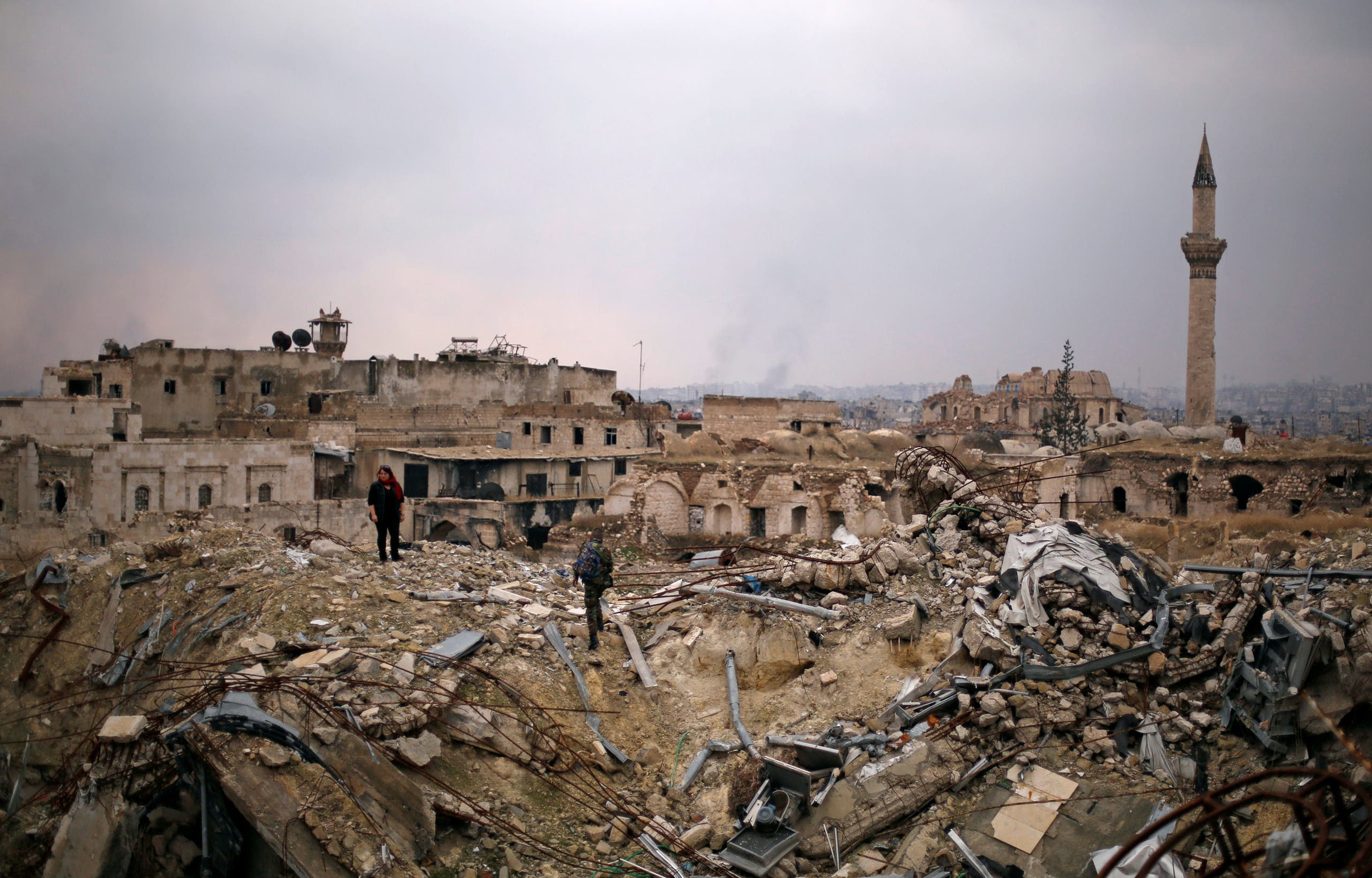A member of forces loyal to Syria's President Bashar al-Assad stands with a civilian on the rubble of the Carlton Hotel, in the government controlled area of Aleppo, Syria December 17, 2016