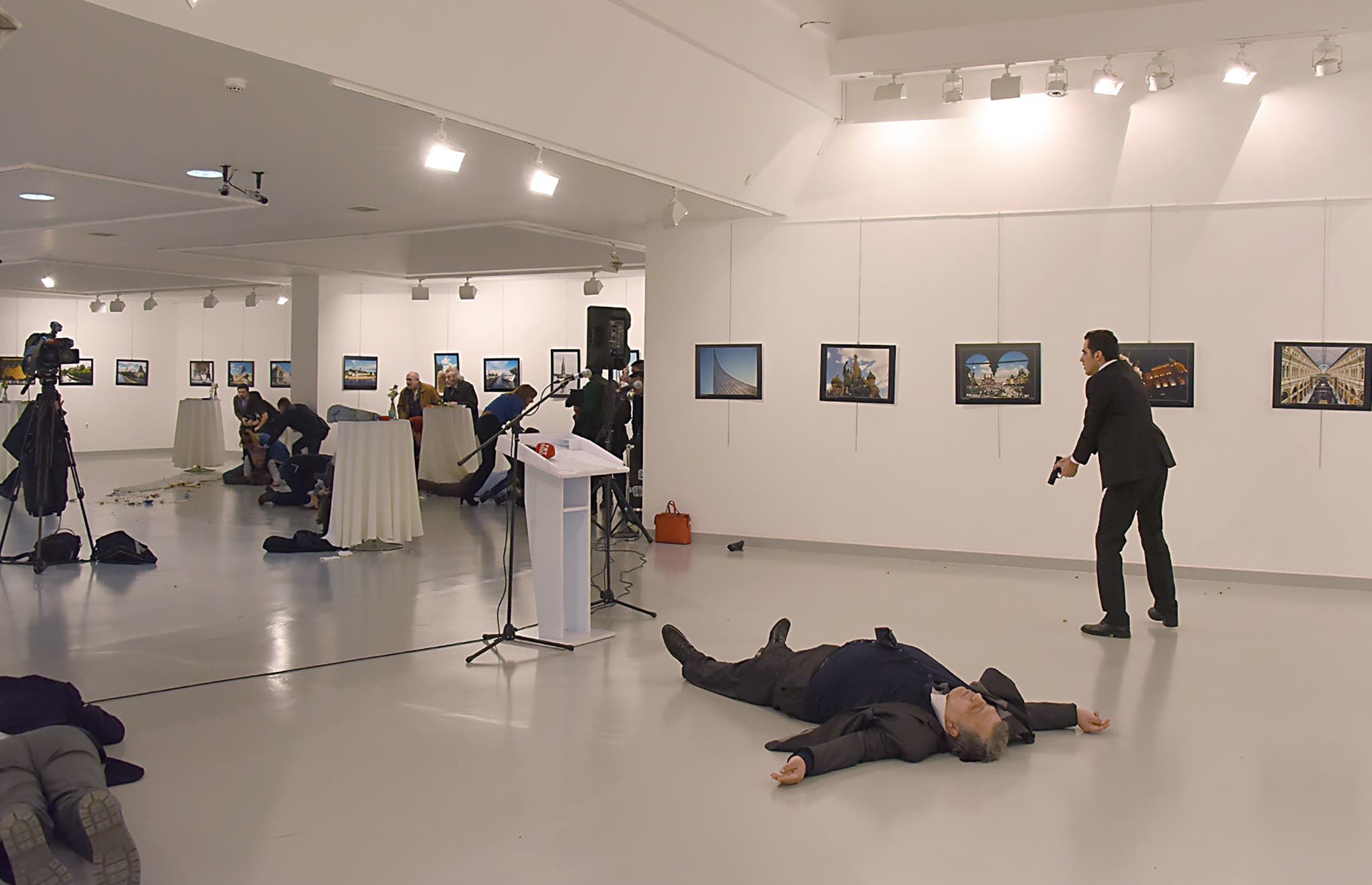 This picture taken on December 19, 2016 shows Andrey Karlov (2ndR), the Russian ambassador to Ankara, lying on the floor after being shot by a gunman (R) during an attack during a public event in Ankara. AFP