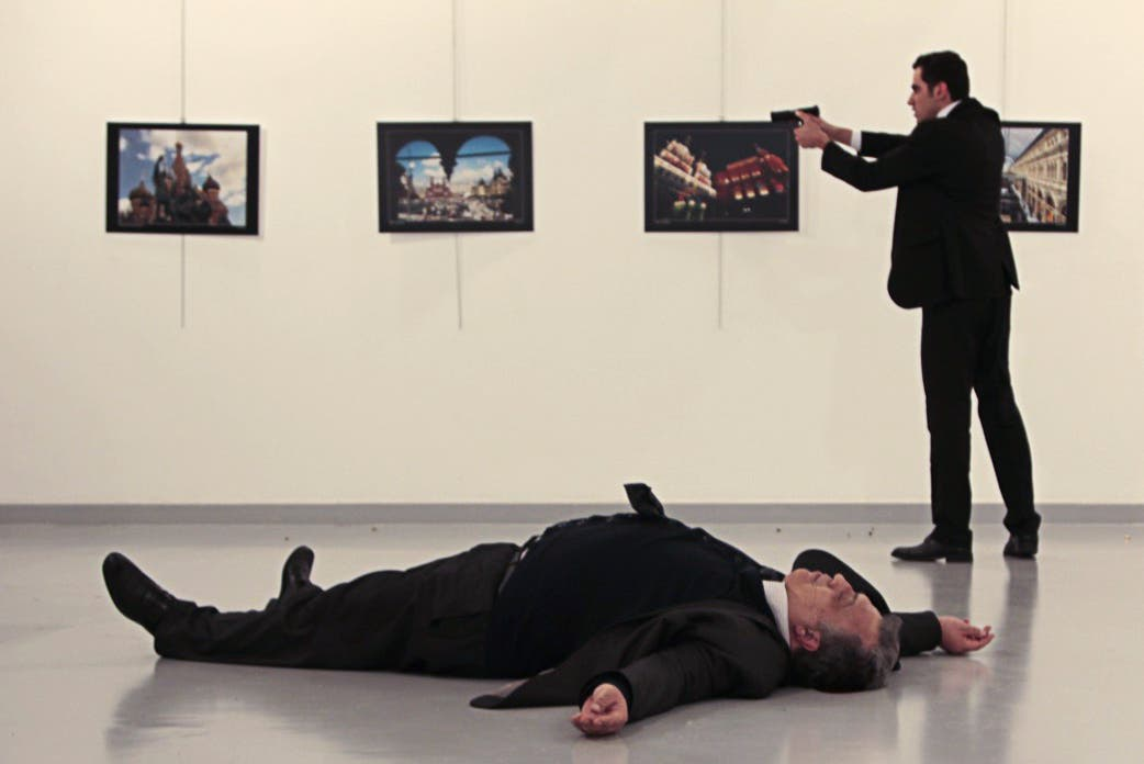 This picture taken on December 19, 2016 shows Andrey Karlov (bottom), the Russian ambassador to Ankara, lying on the floor after being shot by a gunman (R) during an attack during a public event in Ankara. (AFP)