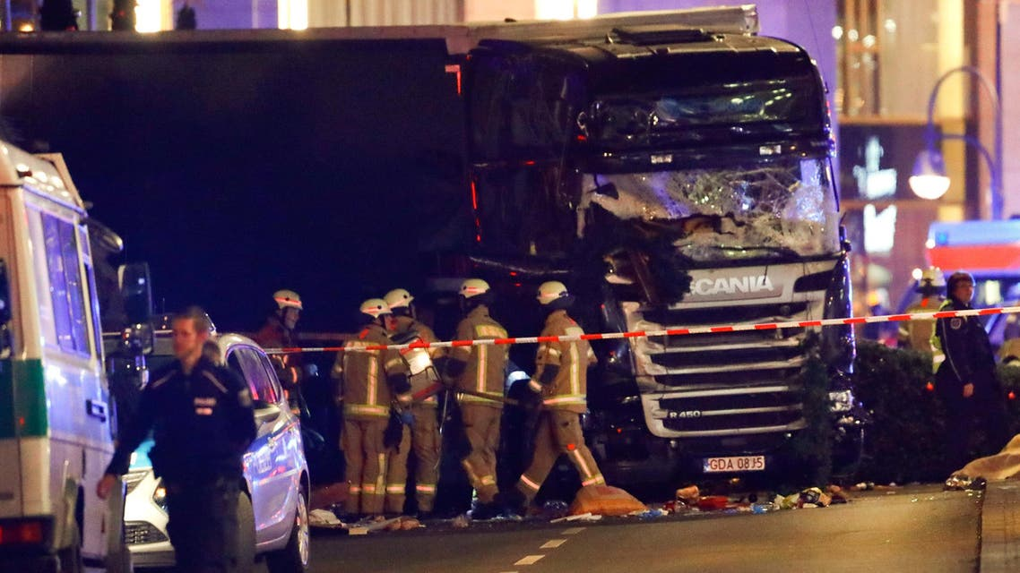 Police and emergency workers stand next to a crashed truck at  a Christmas market in the west of Berlin, Germany, on December 19, 2016. (Reuters)