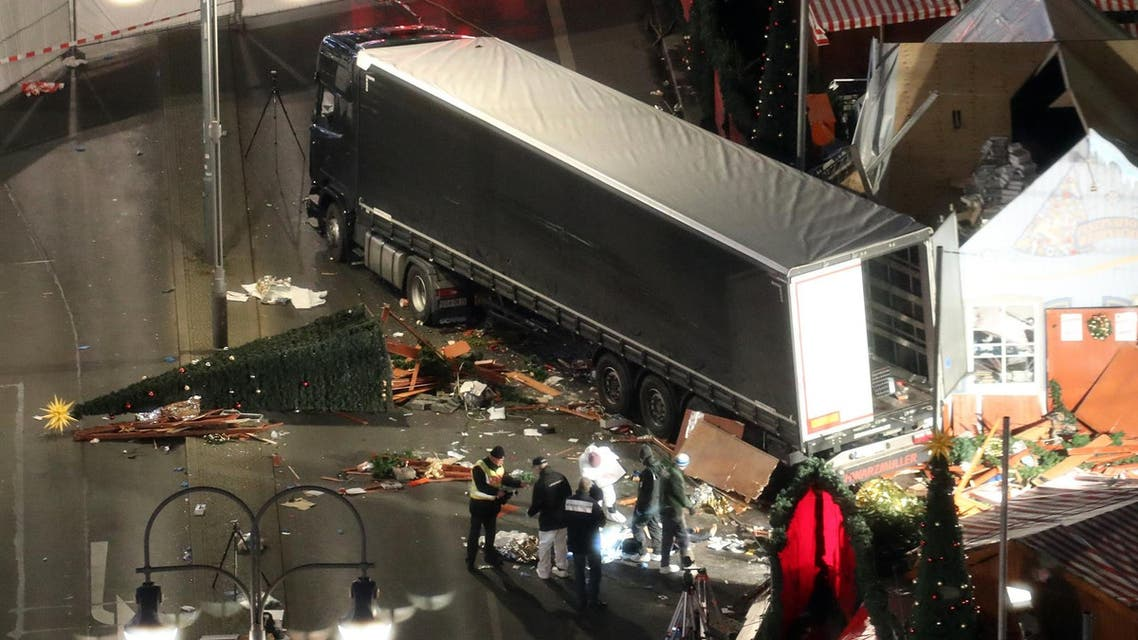 Police search the surroundings of a truck which run into a crowded Christmas market the evening before and killed several people in Berlin, Germany, early Tuesday, Dec. 20, 2017. (Michael Kappeler/dpa via AP)
