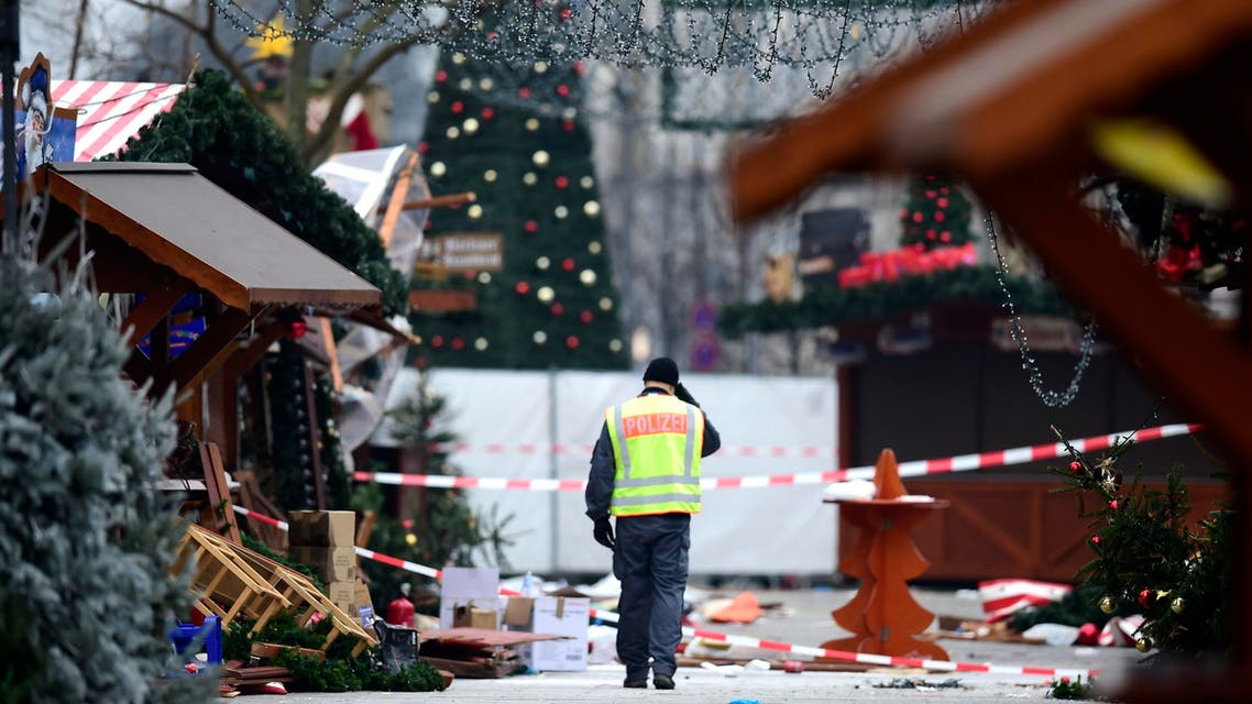"""A policeman walks at the Christmas market near the Kaiser-Wilhelm-Gedaechtniskirche (Kaiser Wilhelm Memorial Church), the day after a terror attack, in central Berlin, on December 20, 2016. German police said they were treating as """"a probable terrorist attack"""" the killing of 12 people when the speeding lorry cut a bloody swath through the packed Berlin Christmas market. Tobias SCHWARZ / AFP"""
